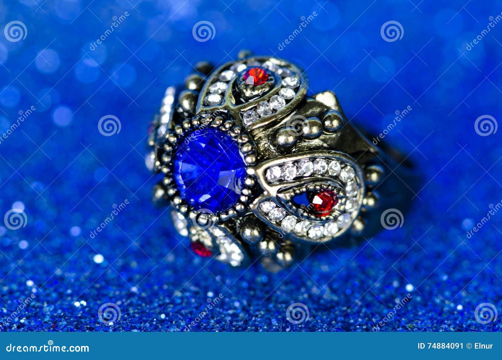 O anel da joia contra o fundo azul