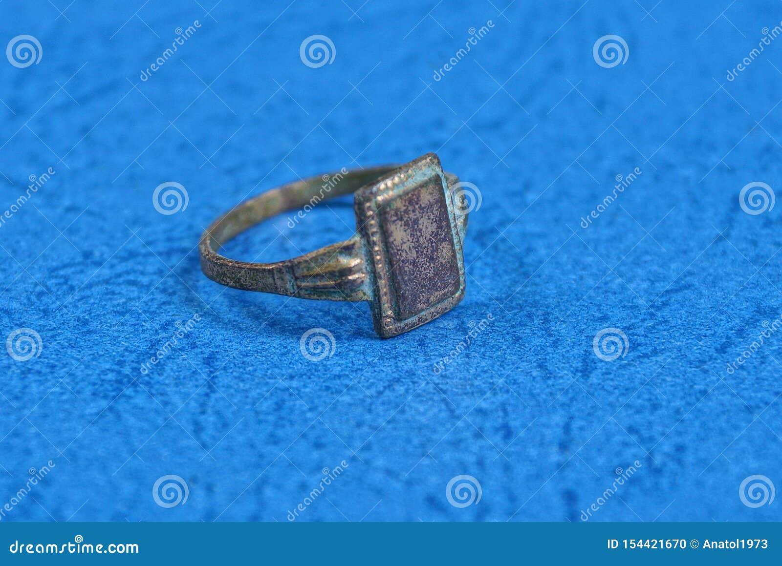 O anel gasto velho amarelo encontra-se em uma tabela azul