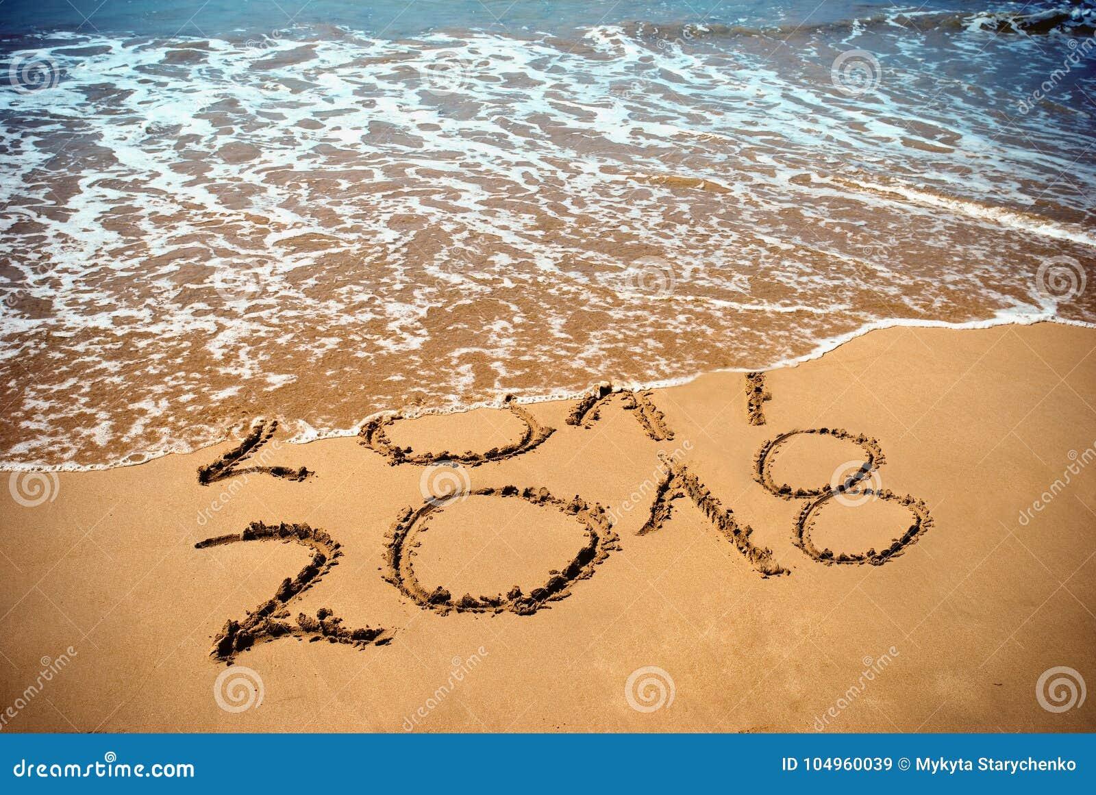 O ano novo 2018 é conceito de vinda - a inscrição 2017 e 2018 em uma areia da praia, a onda está cobrindo os dígitos 2017 Celebri