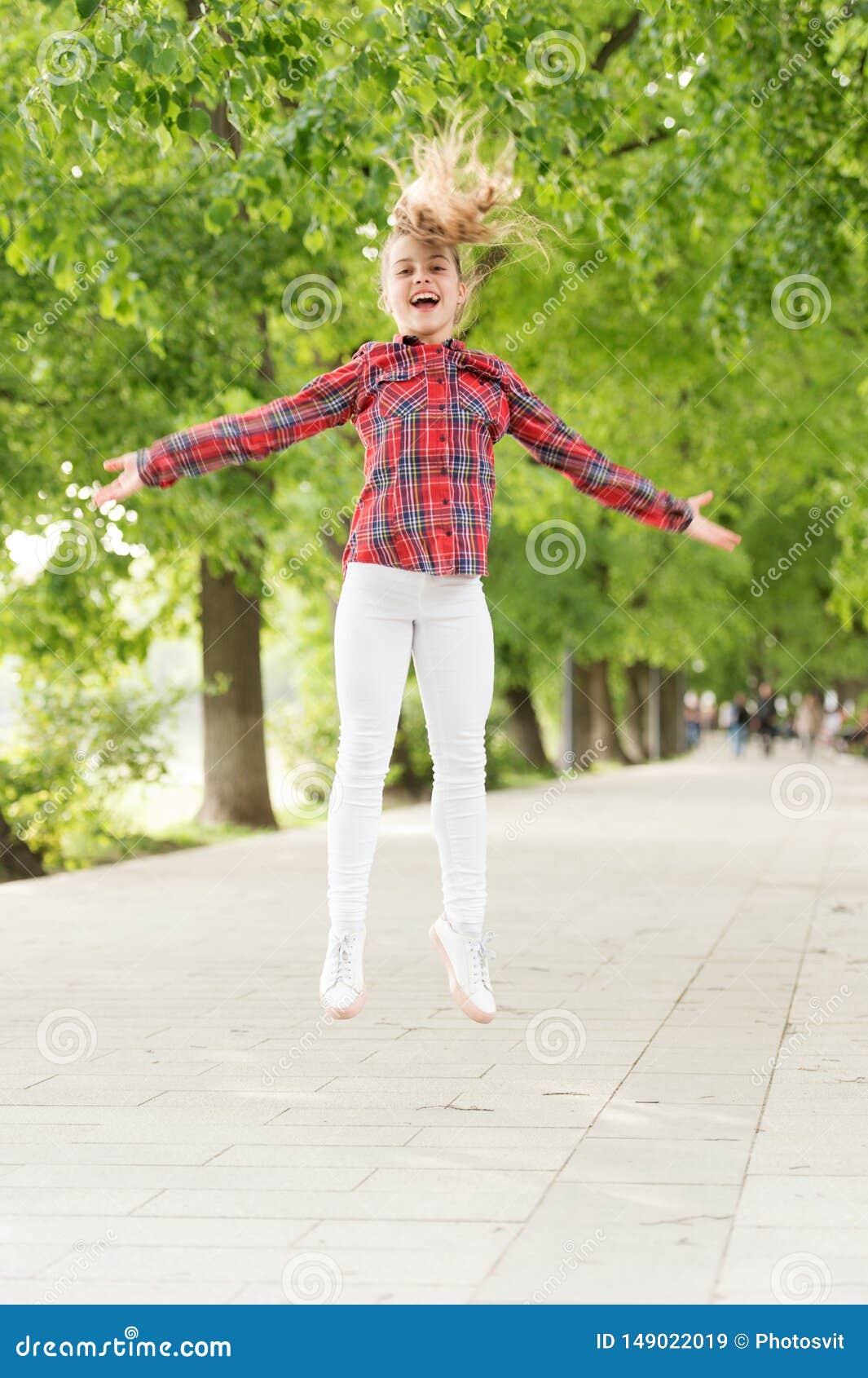 O ar fresco dá-lhe a energia vital De alta energia ou criança agitado Menina pequena que salta no ajuste ocasional para energétic