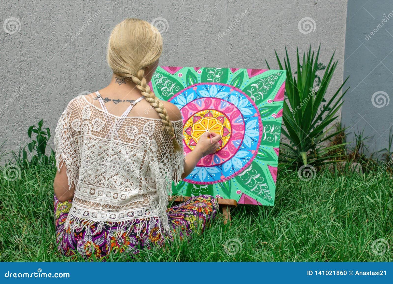 O ar livre da pintura, um louro da jovem mulher tira uma mandala na natureza que senta-se na grama