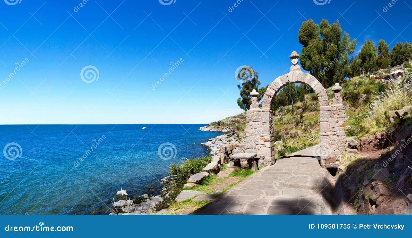 O arco da pedra da entrada na ilha de Taquile, Peru do sul