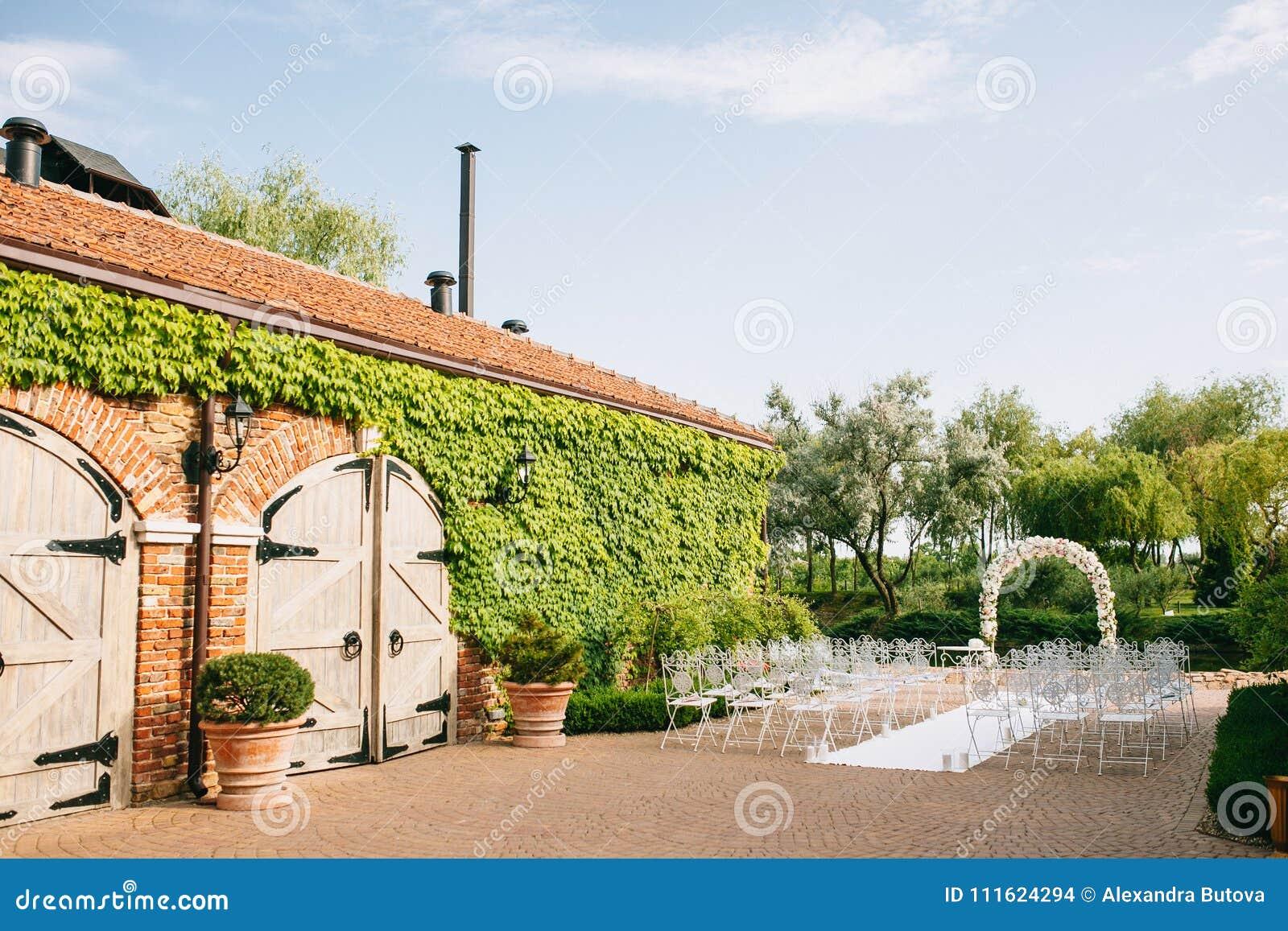 O arco do casamento é decorado com as flores por rosas ao lado da construção antiga do celeiro Com cadeiras do vintage em uma lag