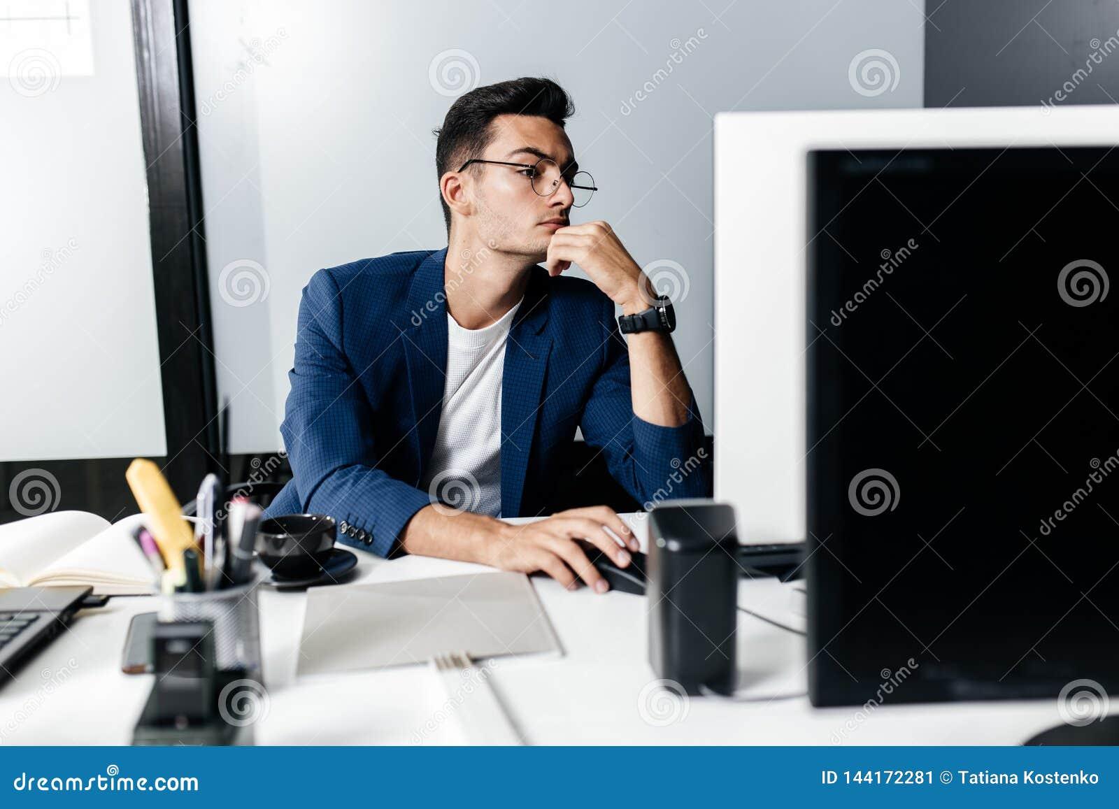 O arquiteto do homem novo nos vidros vestidos em um terno de negócio senta-se em uma mesa na frente de um computador no escritóri