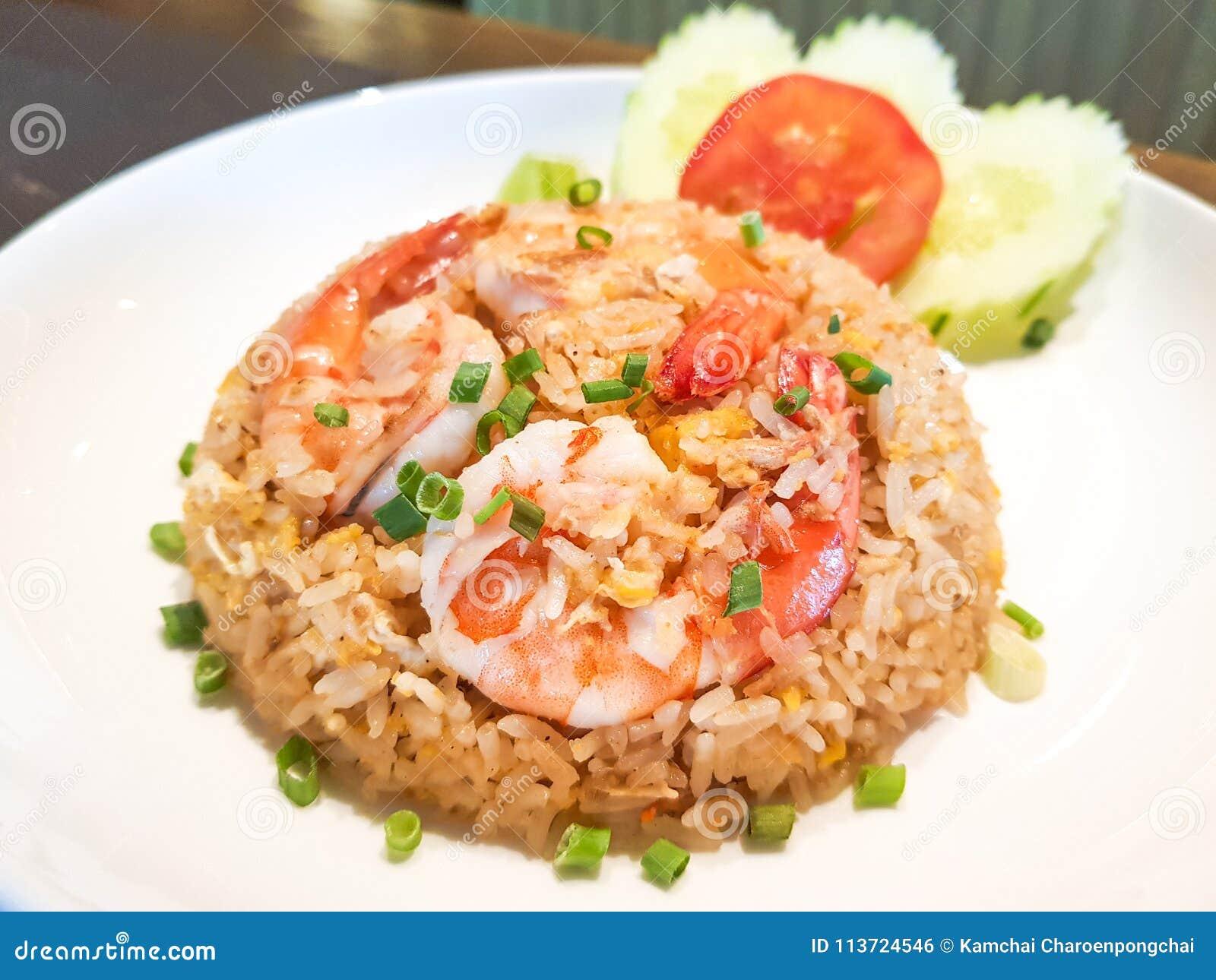 O arroz fritado da gordura dos camarões decora com pepinos e tomate da fatia na parte superior com camarões