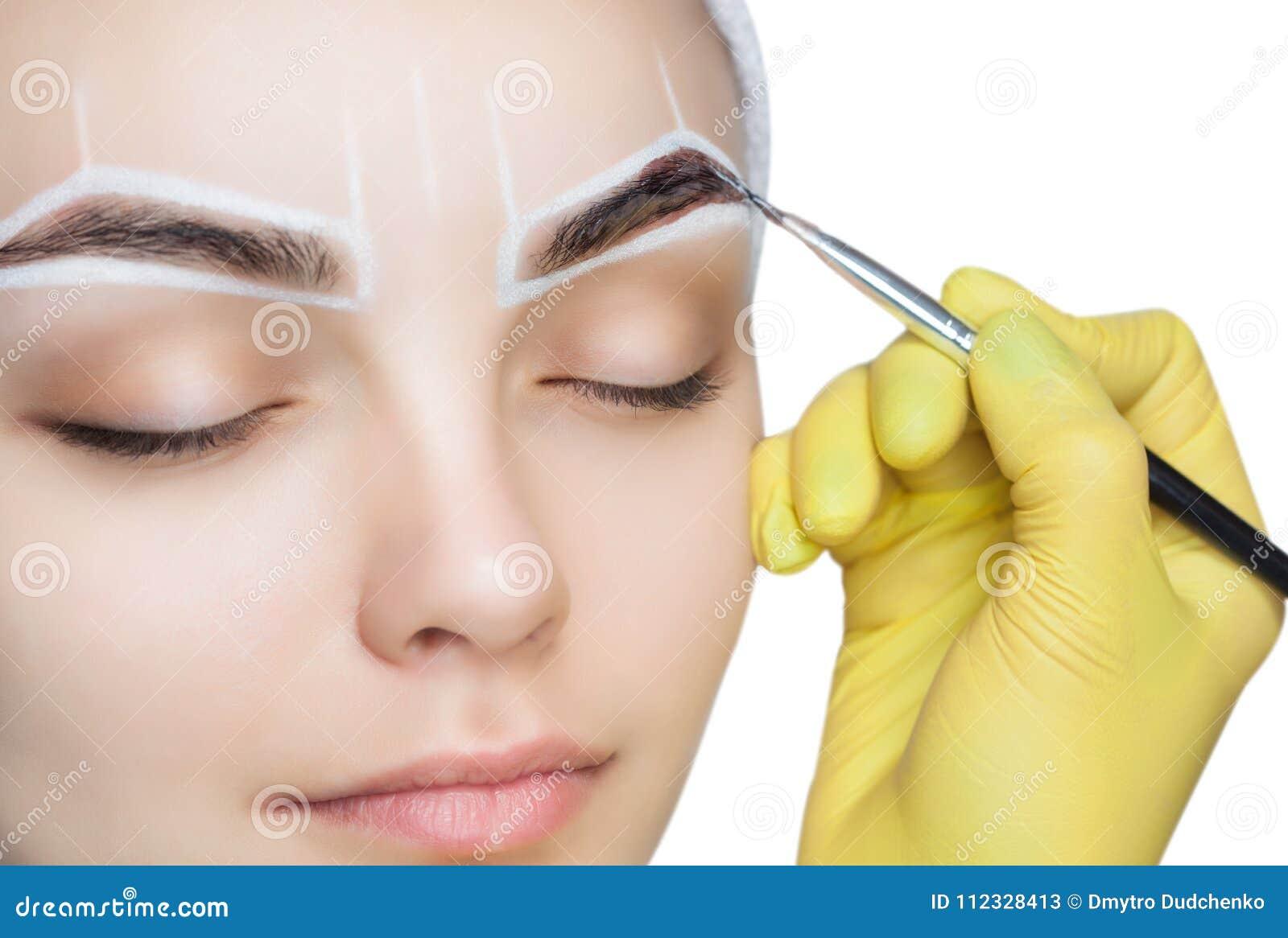 O artista de composição aplica uma tintura da sobrancelha das pinturas nas sobrancelhas de uma moça