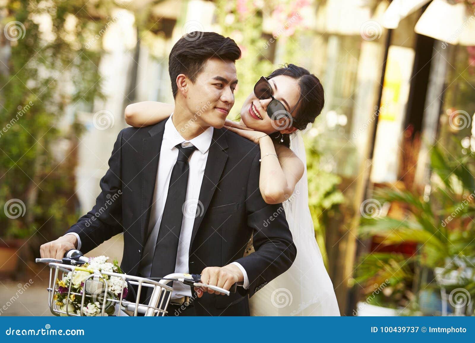 O asiático wed recentemente os pares que montam uma bicicleta