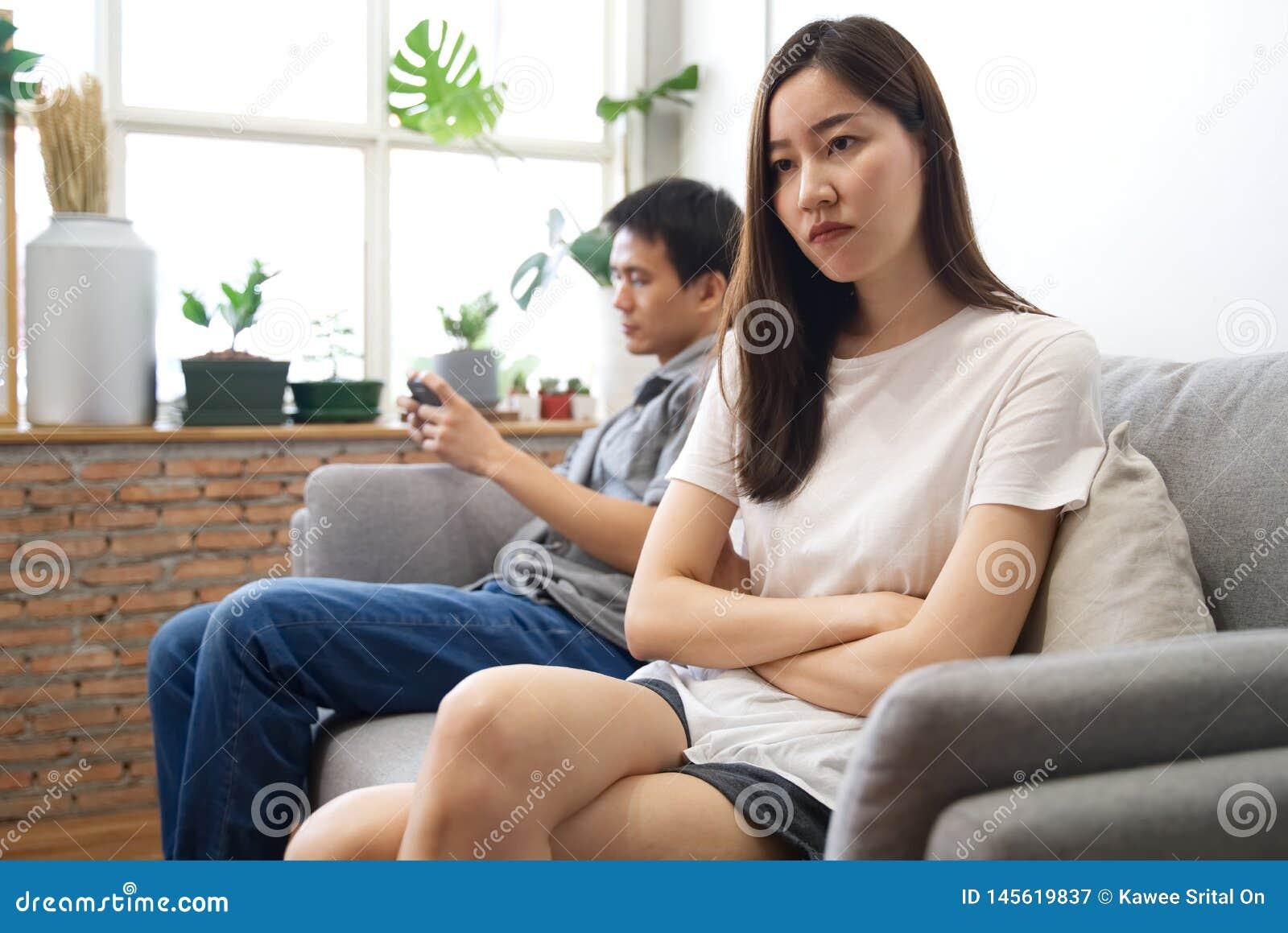 O assento da moça no sofá está sentindo irritado seu noivo