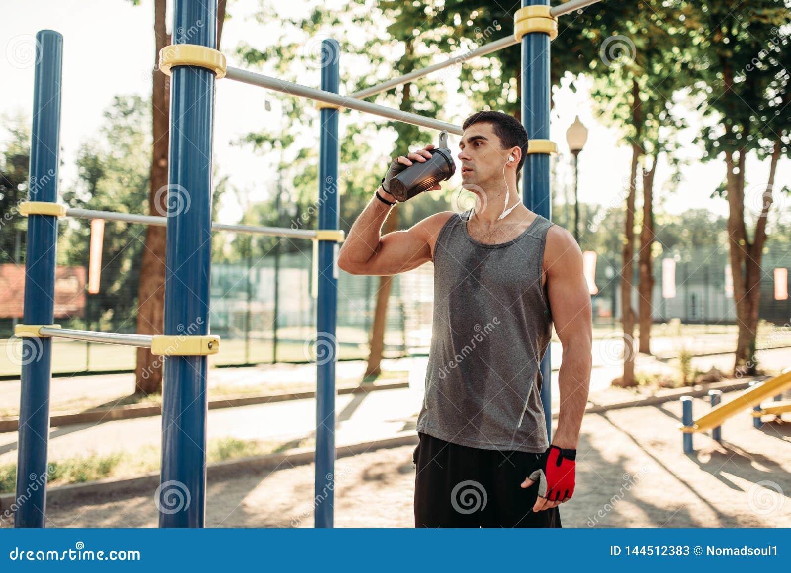 O atleta masculino bebe a água após o treinamento exterior