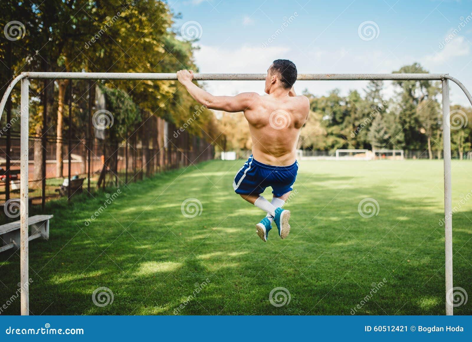 O atleta masculino que faz a tração levanta, queixo levanta no parque Homem atheltic da aptidão que dá certo e que treina no parq