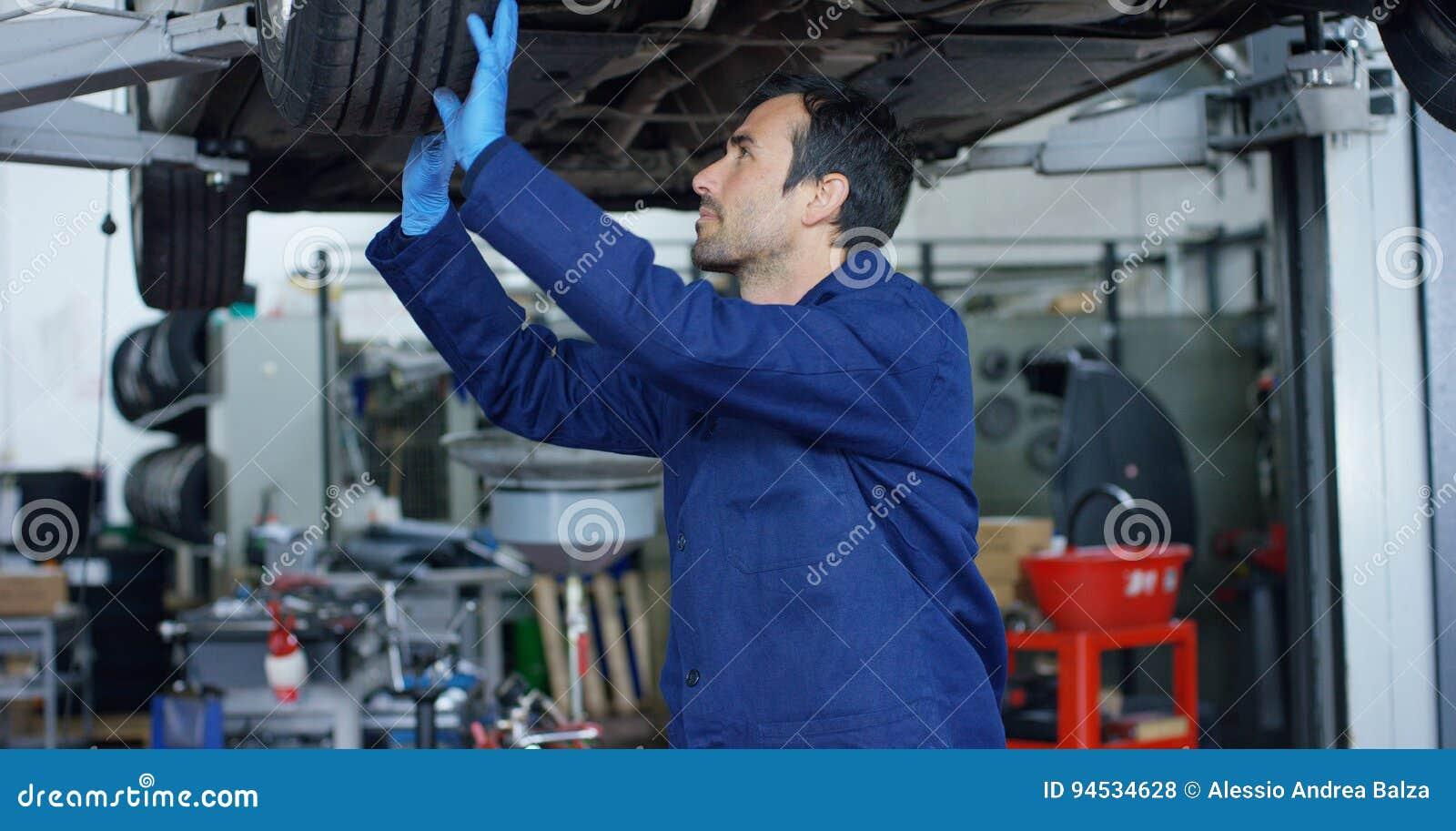 O auto mecânico no serviço do carro, reparos do especialista o carro, faz a transmissão e as rodas Conceito: reparo das máquinas,