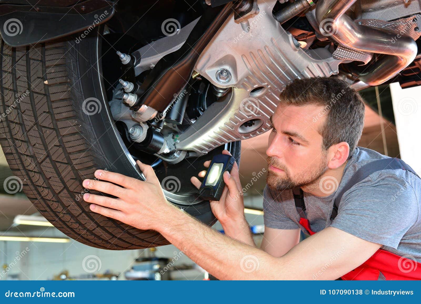 O auto mecânico repara o veículo em uma oficina