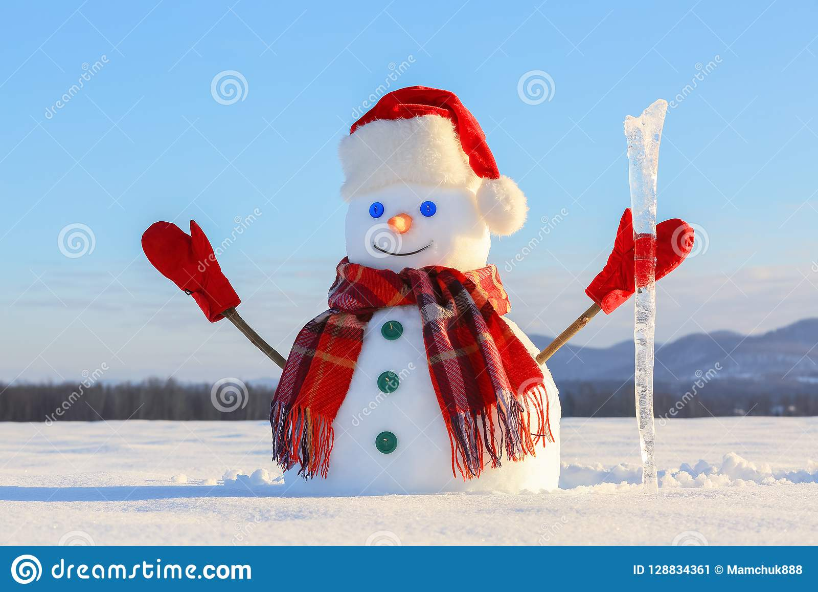 O azul eyed o boneco de neve de sorriso no chapéu vermelho, luvas e o lenço da manta mantém o sincelo disponivel Manhã fria alegr