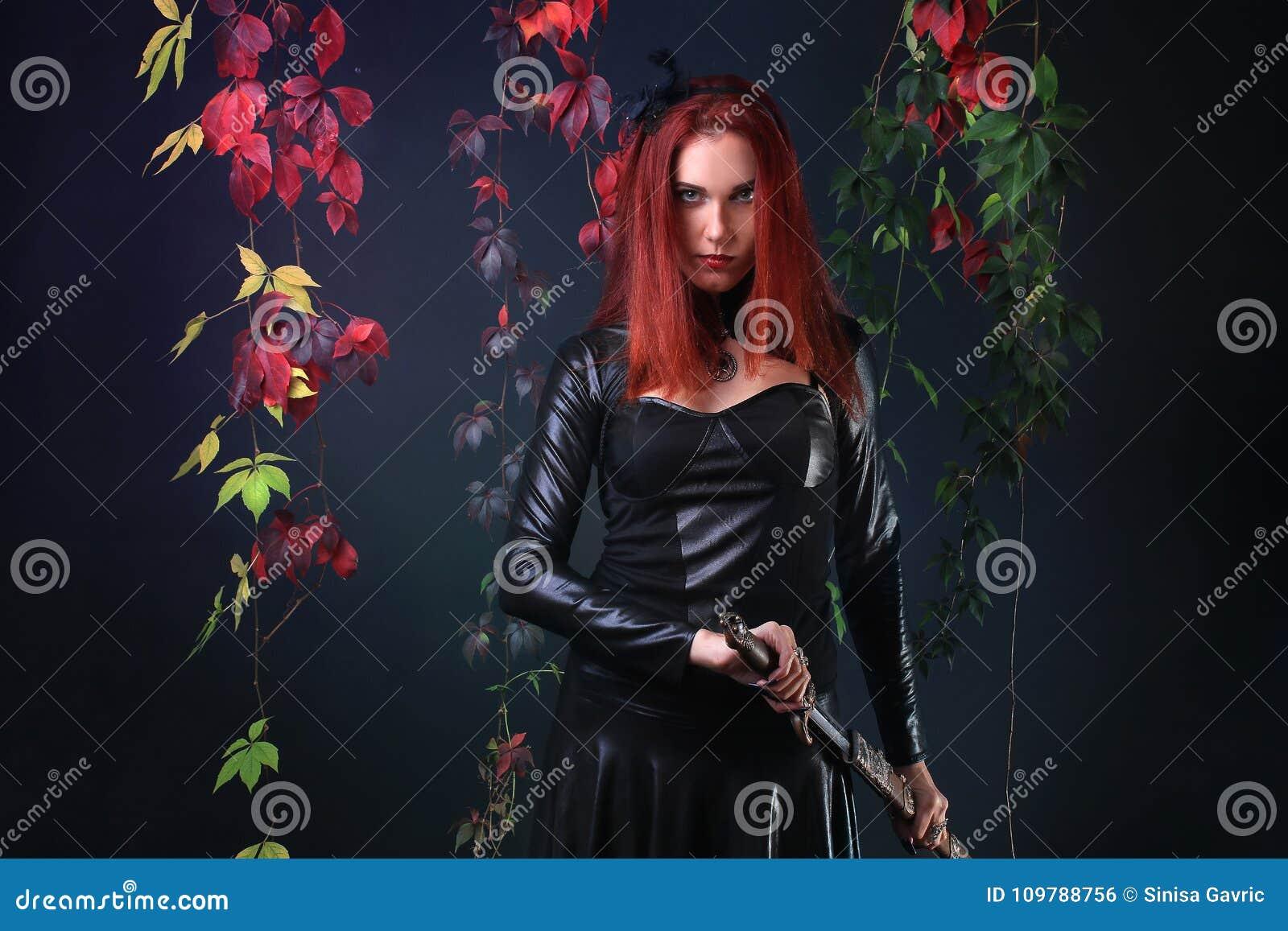 O azul Eyed a menina gótico principal vermelha que retira uma espada da fantasia entre videiras do outono