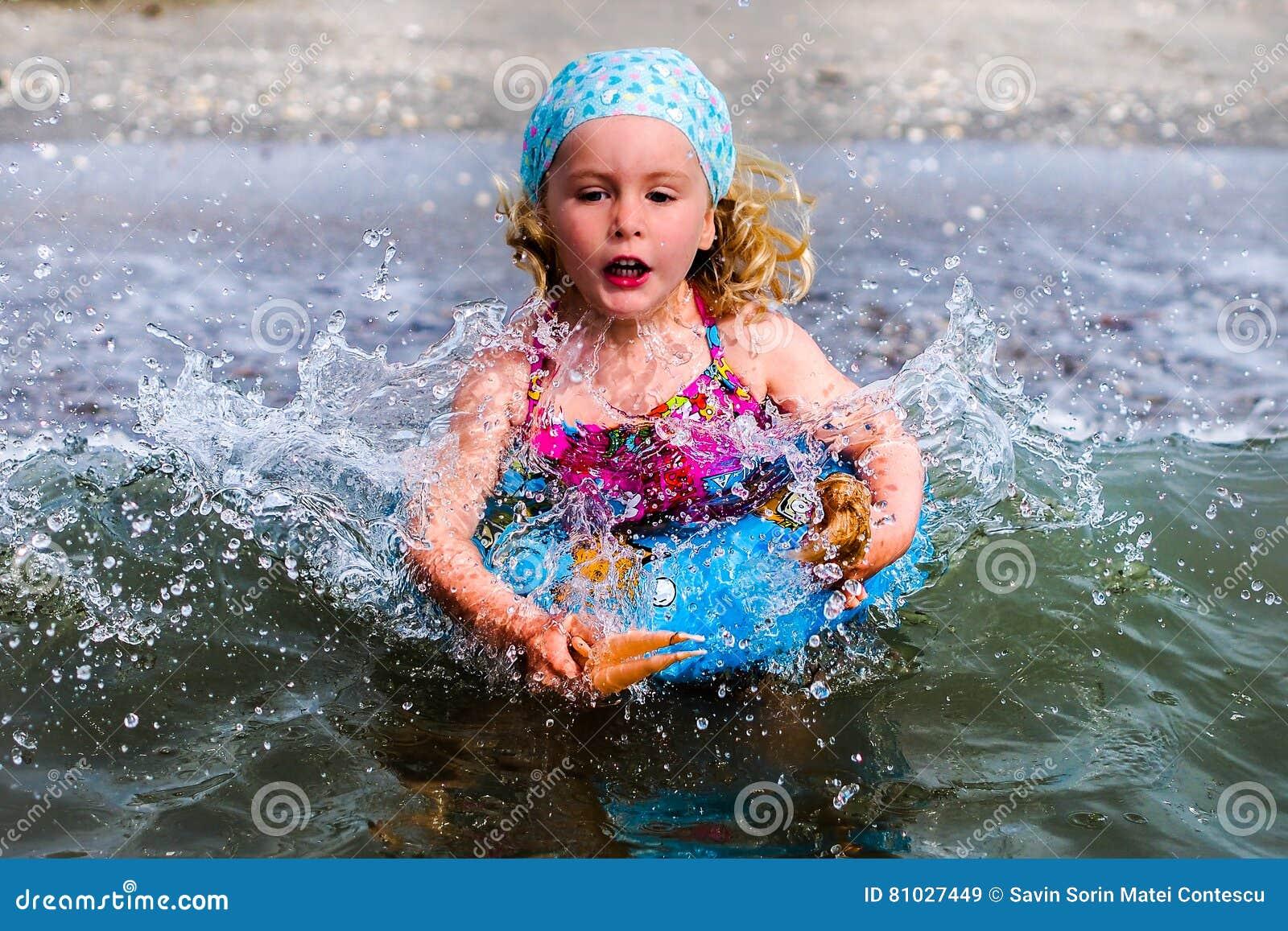 O azul eyed a menina loura que joga na água