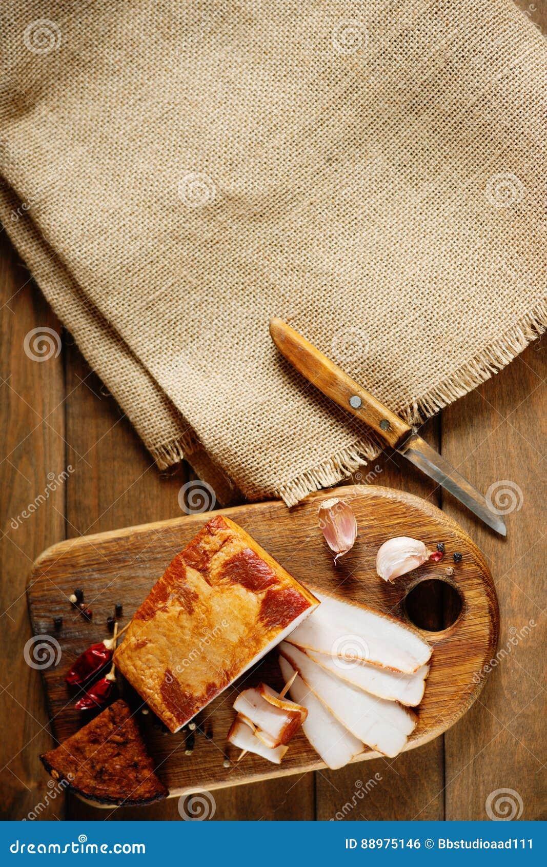 O bacon fumado, faca, cortou o pão e a matéria têxtil da lona