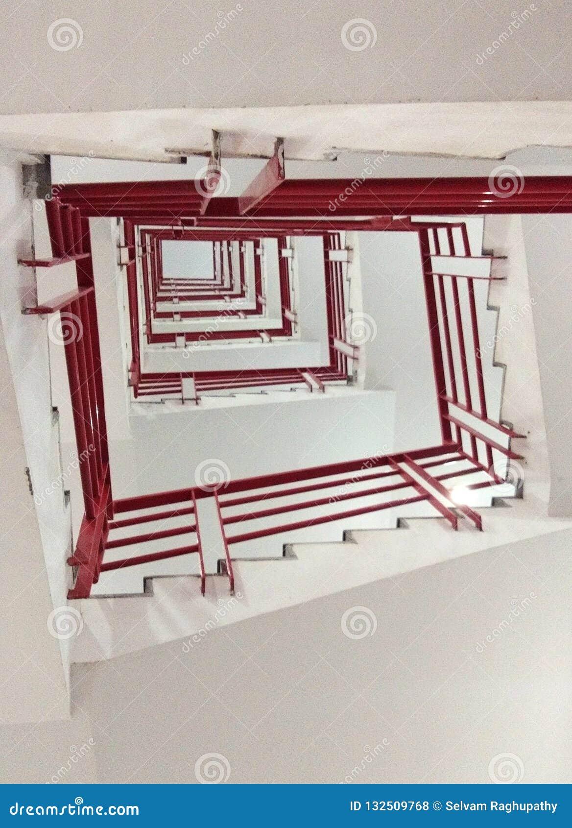 O baixo ângulo de etapas bonitas com a cerca de aço vermelha