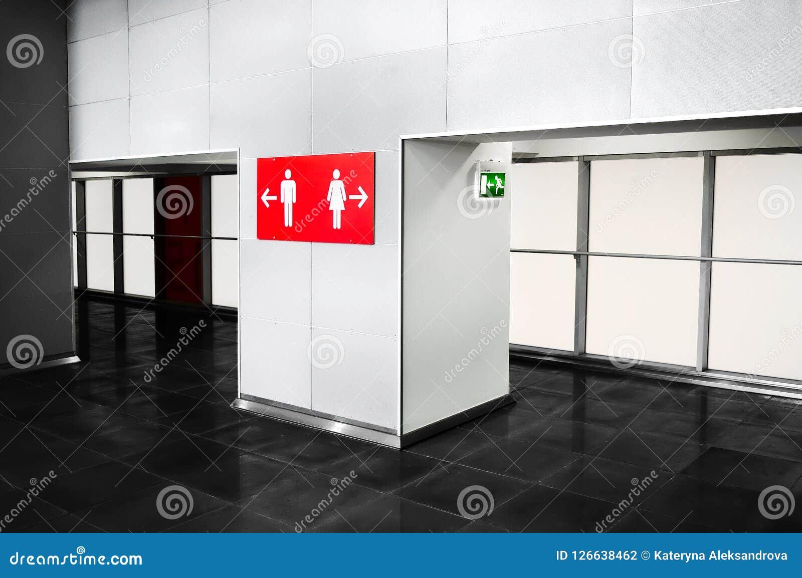 O banheiro do lugar público presta serviços de manutenção ao sinal da indicação Navigat de Toilette
