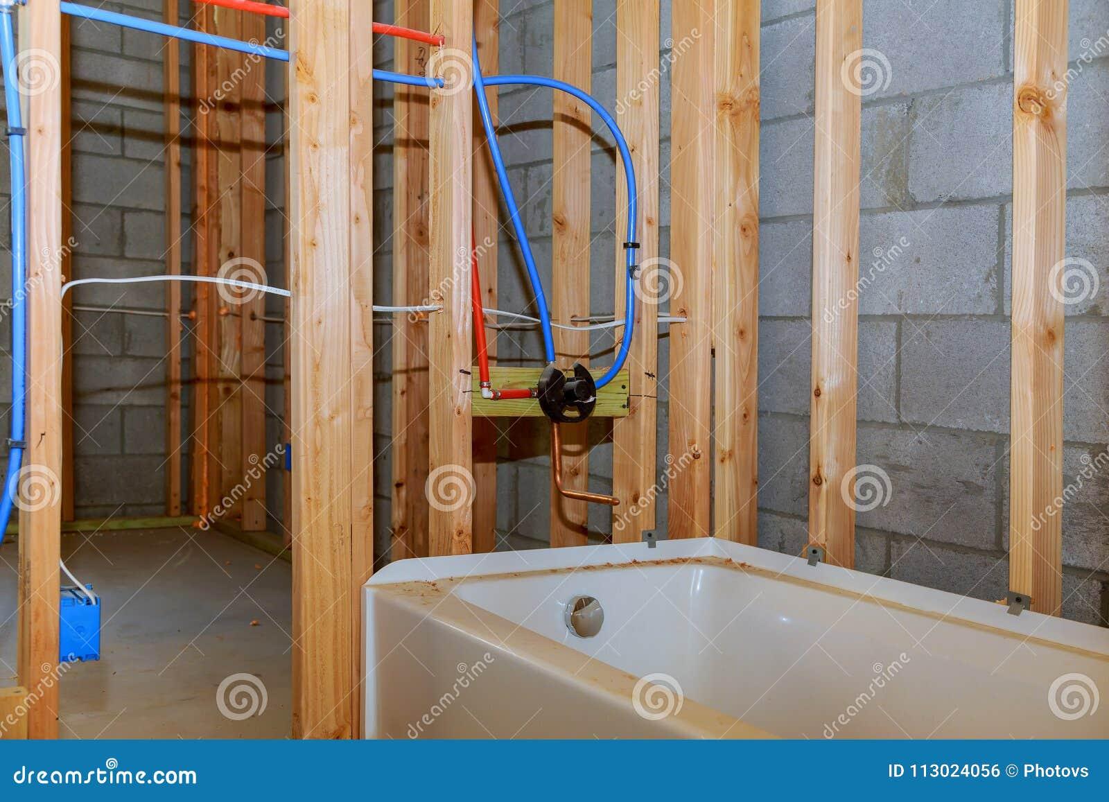 O banheiro remodela mostrar sob a instalação de conexão do trabalho do encanamento do assoalho das tubulações para a água para co