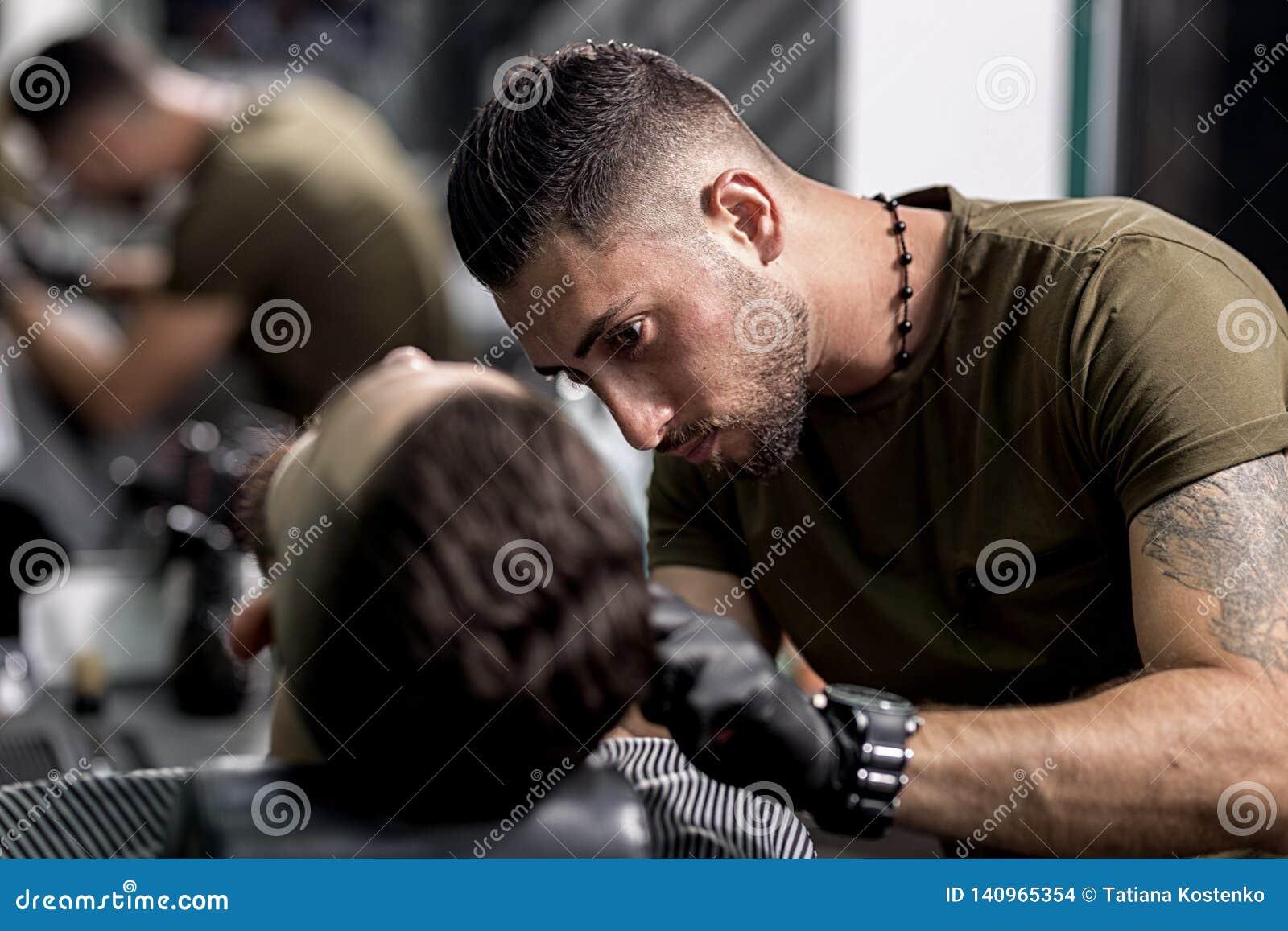 O barbeiro considerável em luvas pretas apara uma barba do homem à moda em um barbeiro