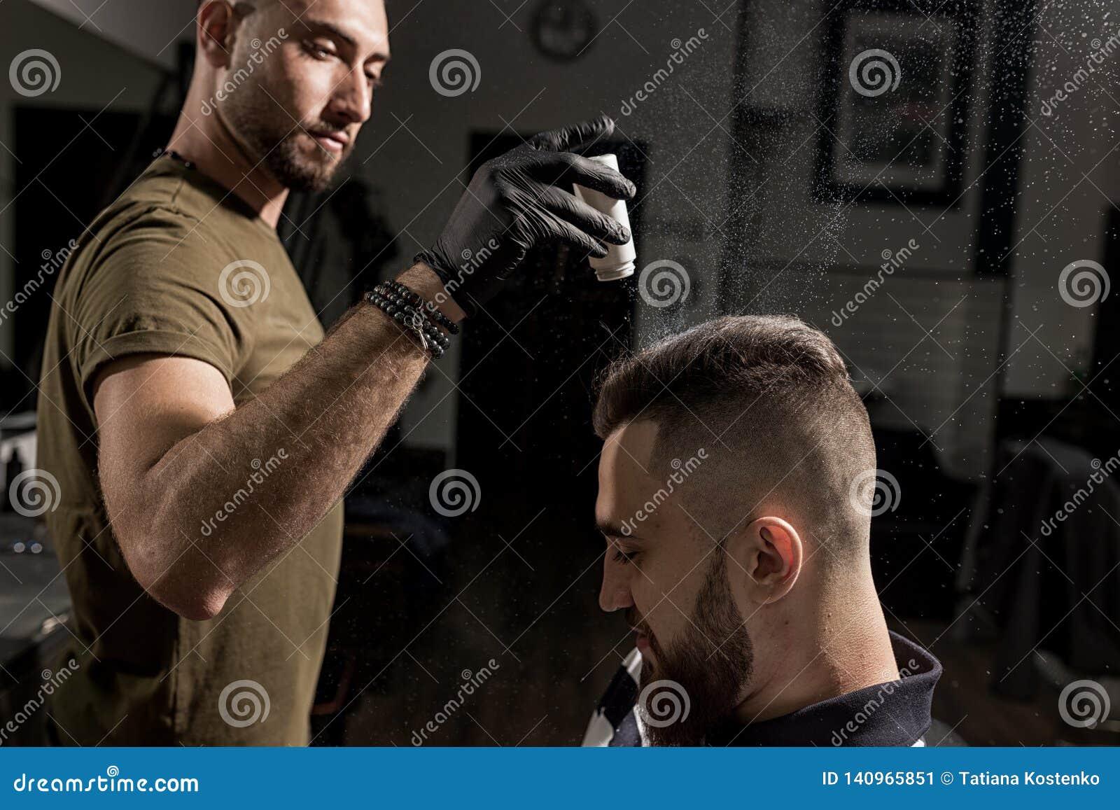 O barbeiro considerável está fixando a denominação do homem novo brutal com um styler seco em um barbeiro