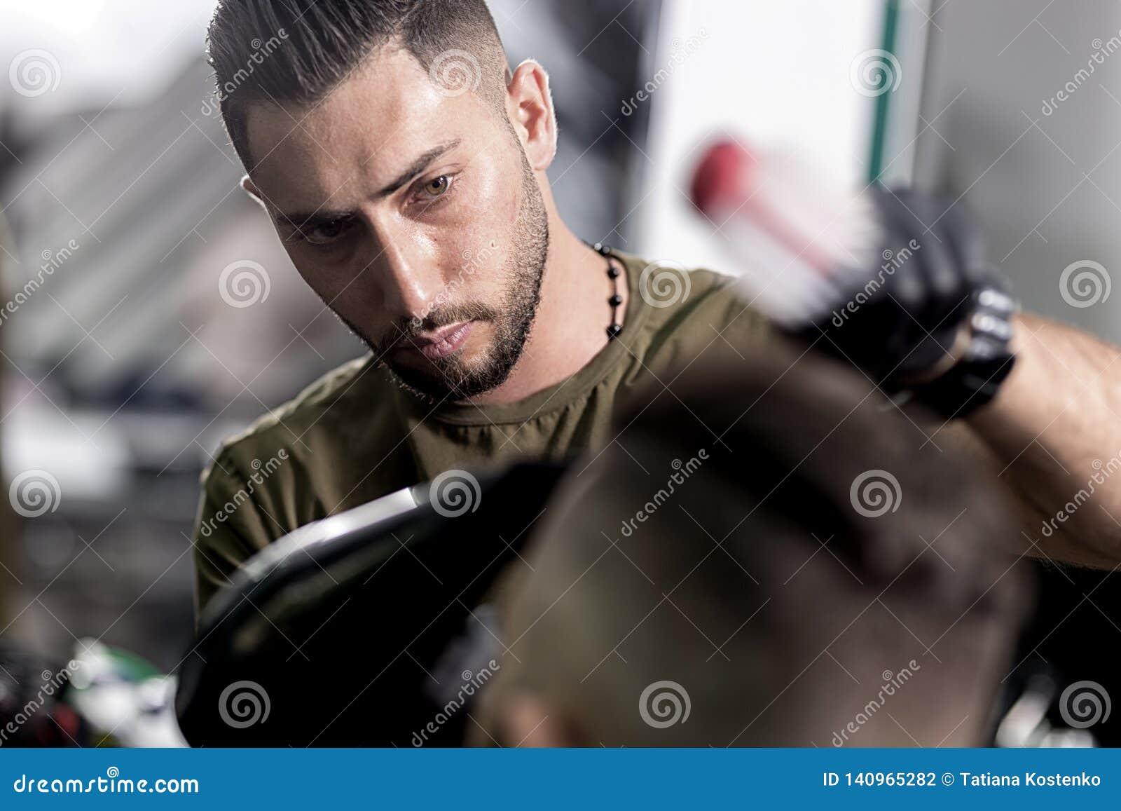 O barbeiro considerável seca o cabelo e faz uma denominação do moreno em um barbeiro