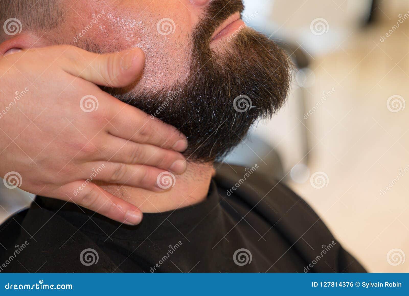 O barbeiro do homem barbeia sua barba