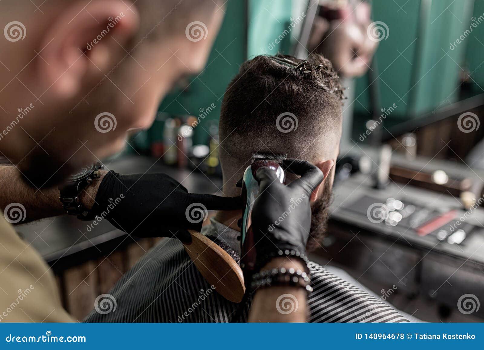 O barbeiro em luvas pretas barbeia os cabelos do homem na parte traseira em uma barbearia