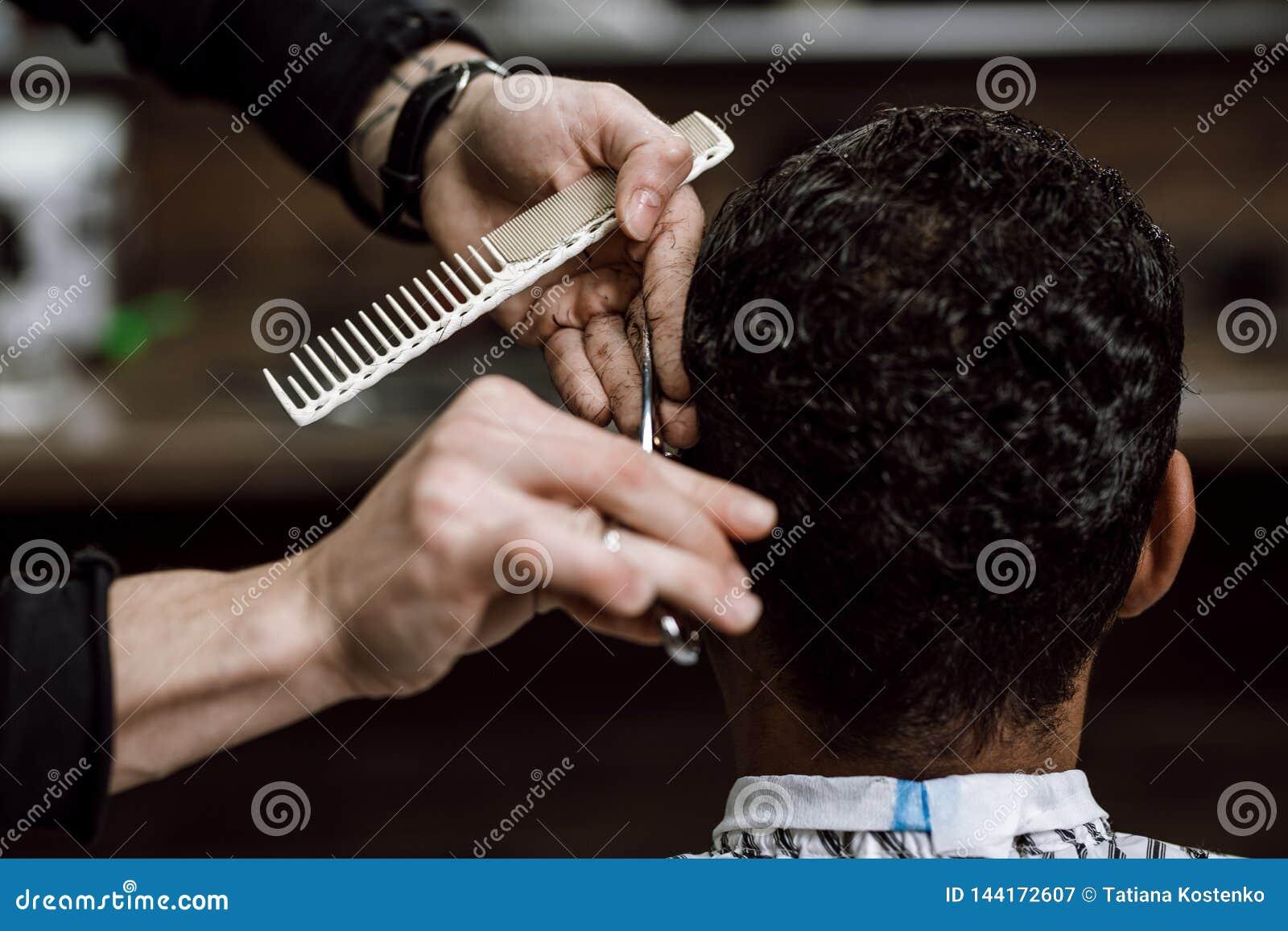 O barbeiro está cortando o cabelo de um homem que guarda tesouras e está penteando-o em suas mãos oposto ao espelho em um barbeir