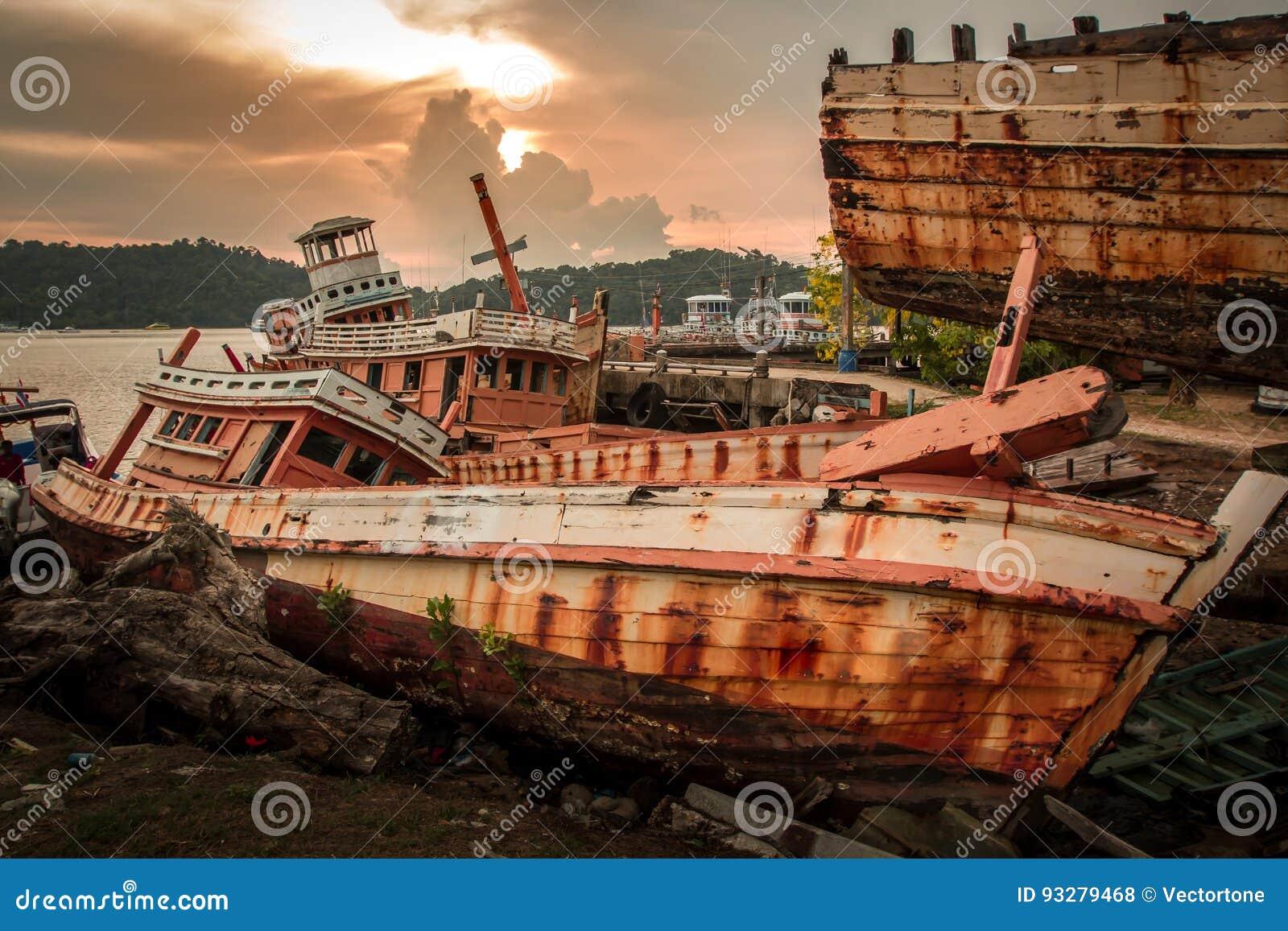 O barco de pesca quebrado saiu abandonado na terra perto do porto