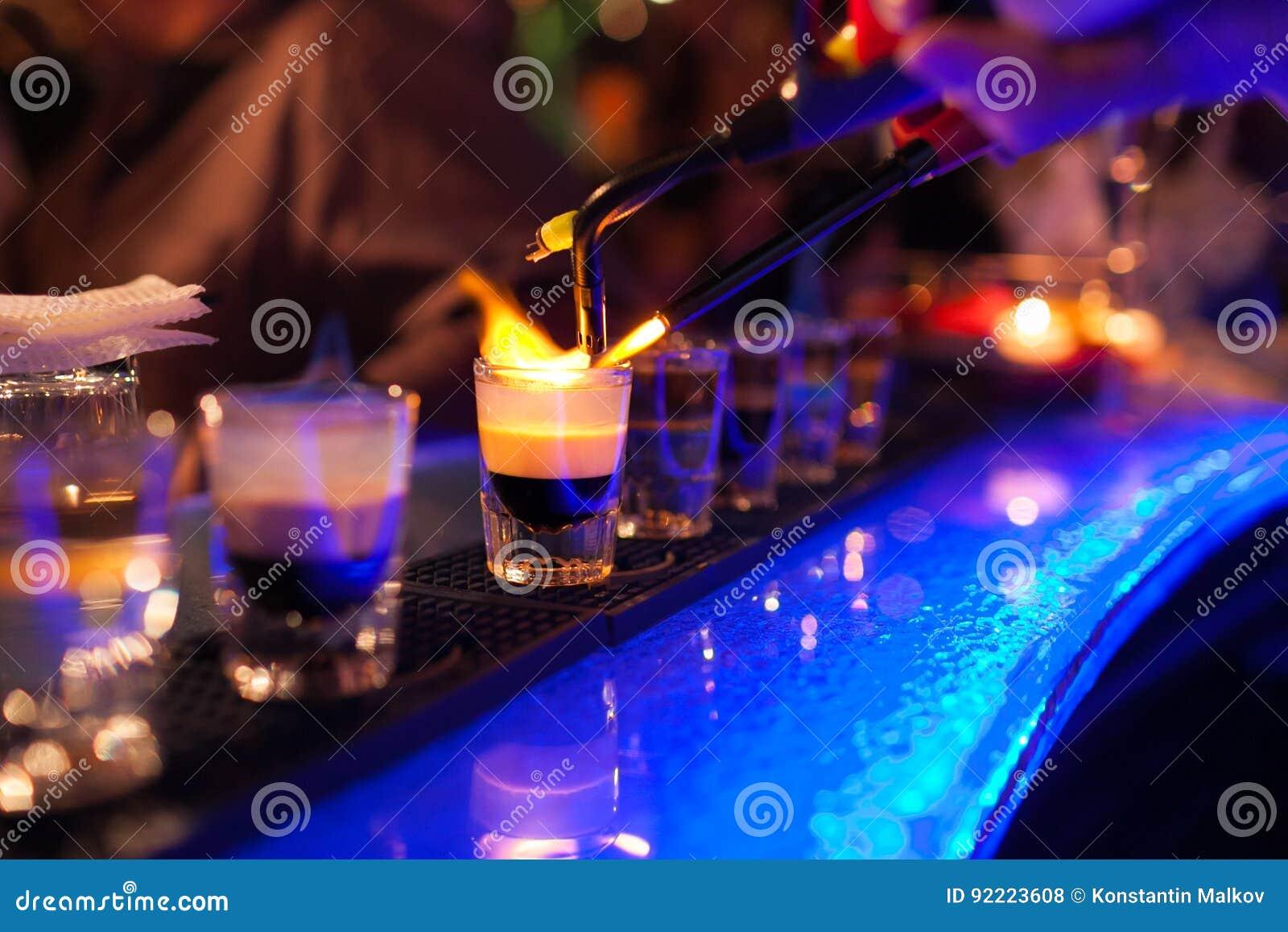 O barman faz o cocktail alcoólico quente e inflama a barra o clube noturno da elite durante o partido prepara um cocktail impetuo