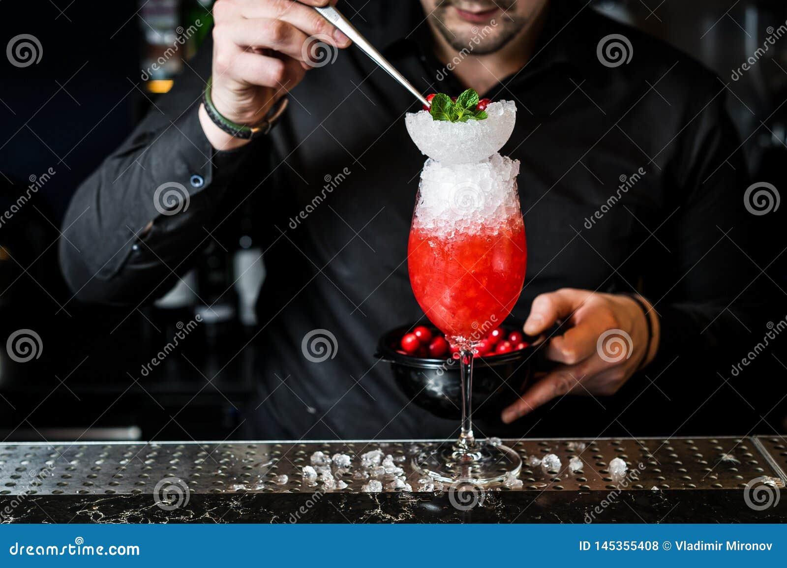 O barman prepara o cocktail de Margarita, fundo escuro, close-up