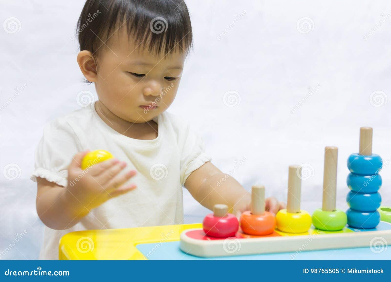 O bebê adorável asiático um ano está jogando a pirâmide colorida do enigma