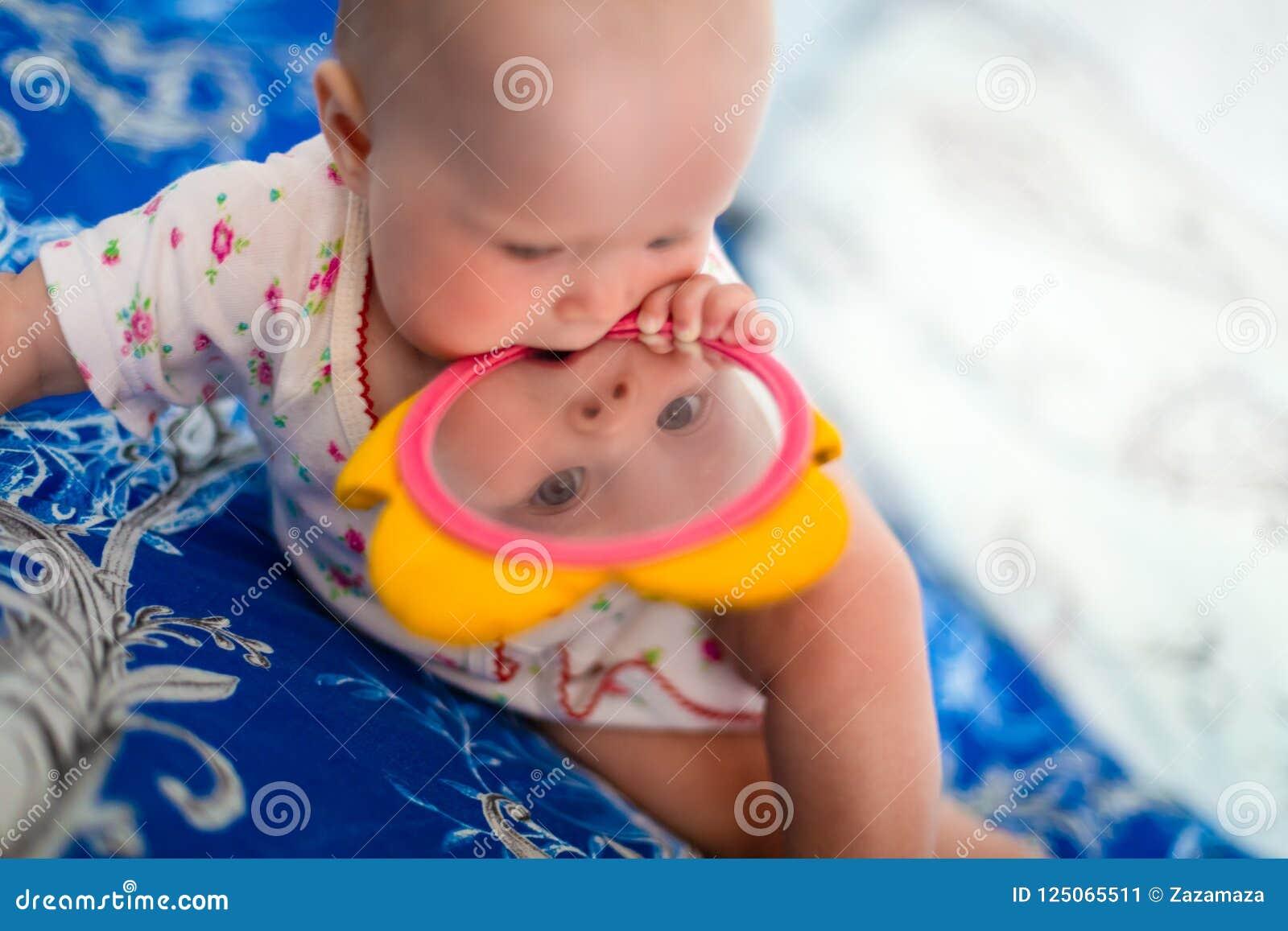 O bebê adorável e bonito senta-se na cama e nos jogos com brinquedos que é espelho das crianças A criança pequena está guardando