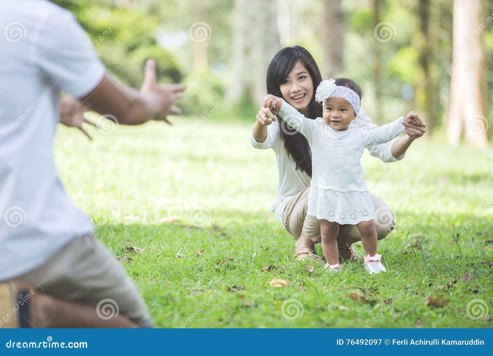 O bebê aprende andar com seu pai no parque