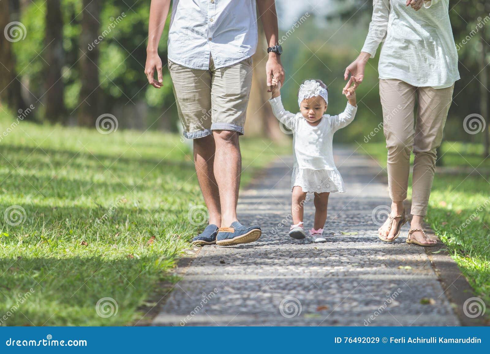 O bebê aprende andar pela primeira vez com seus pais guarda-a