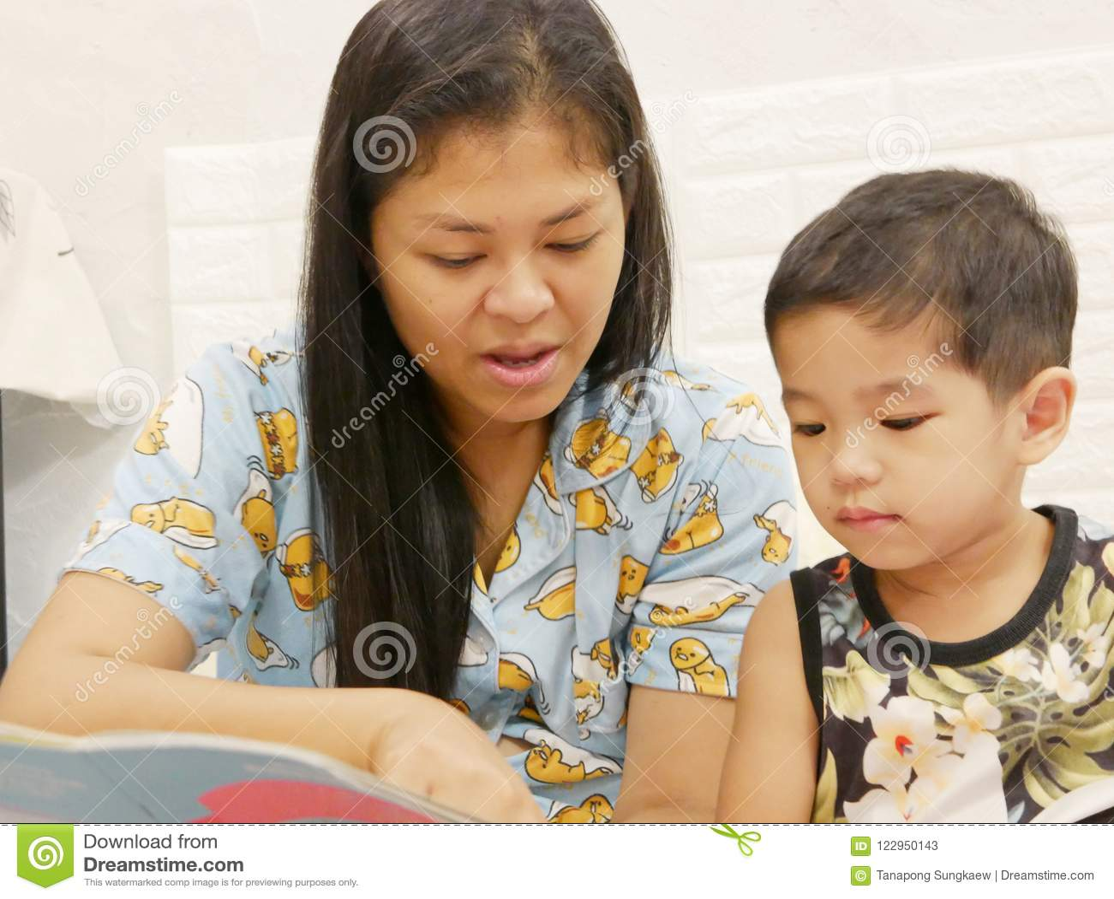 O bebê asiático pequeno aprecia escutar sua mãe que lê um livro alto a ela