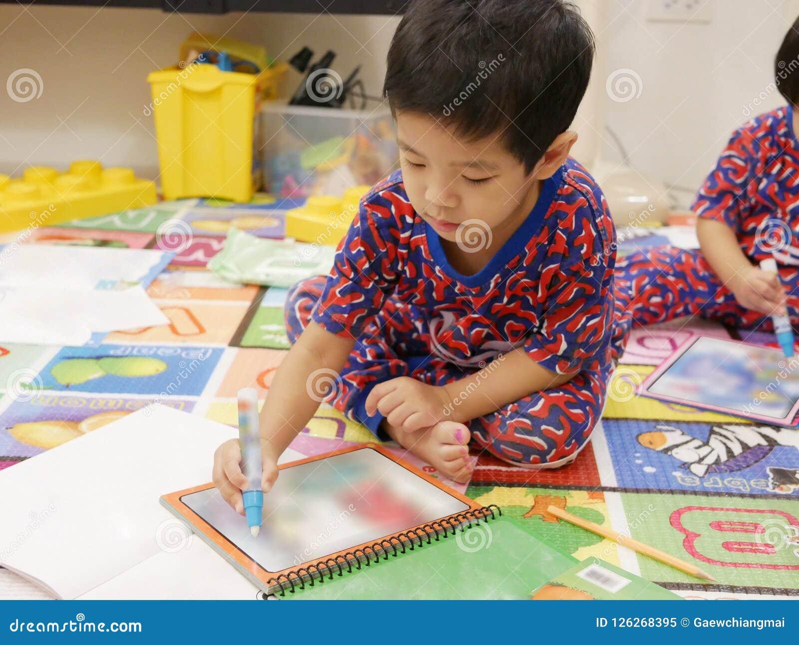 O bebê asiático pequeno deixado aprecia pintar