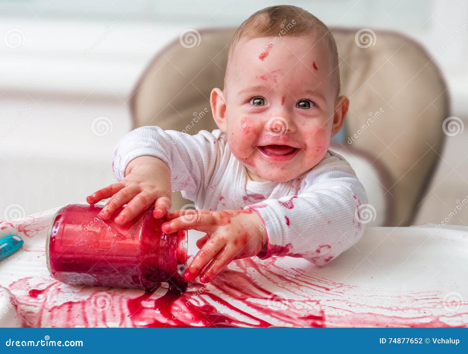 O bebê desarrumado e sujo está comendo o petisco com mãos