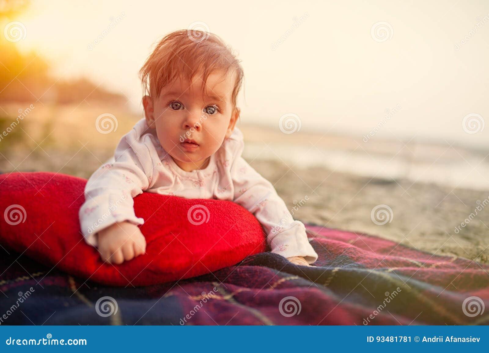 O bebê encontra-se na manta e lê-se o descanso no parque