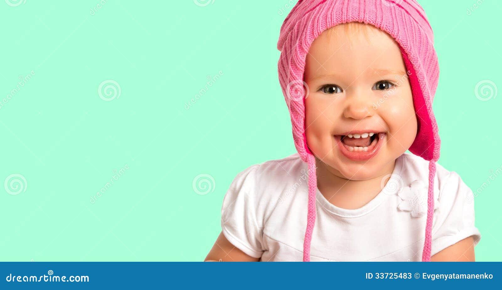 O bebê feliz engraçado em um inverno cor-de-rosa fez malha o riso do chapéu