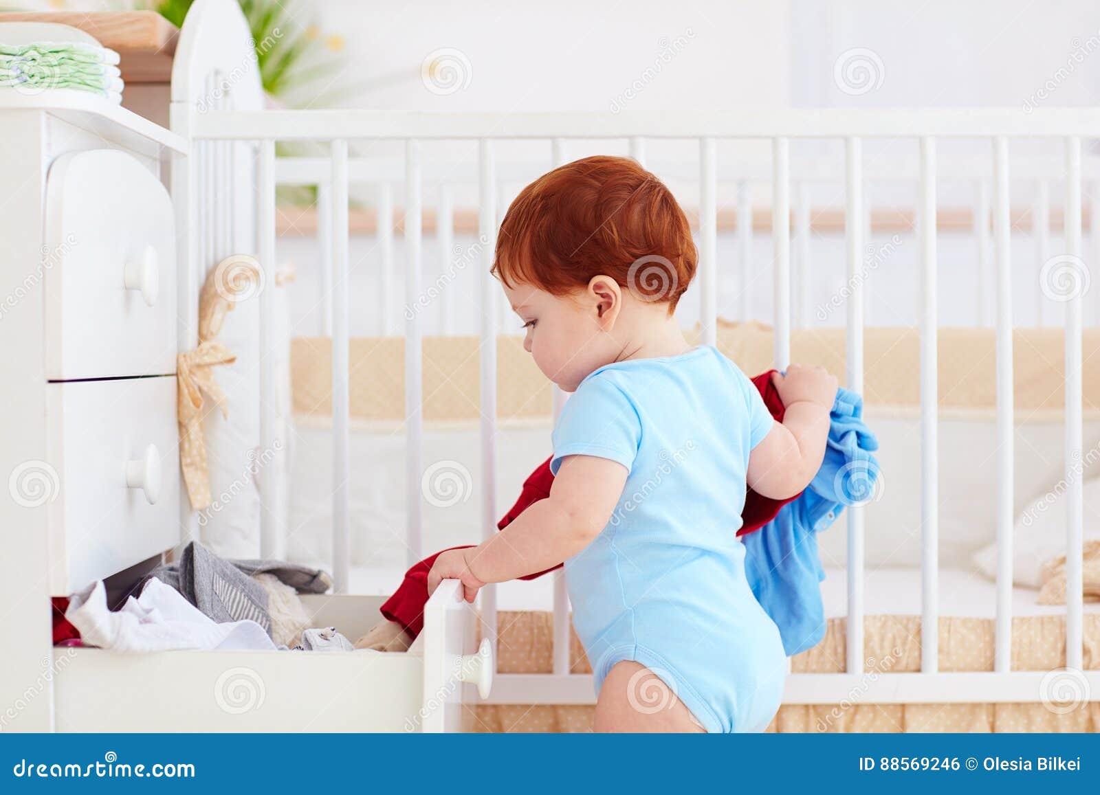 O bebê infantil engraçado que joga para fora veste-se do armário em casa