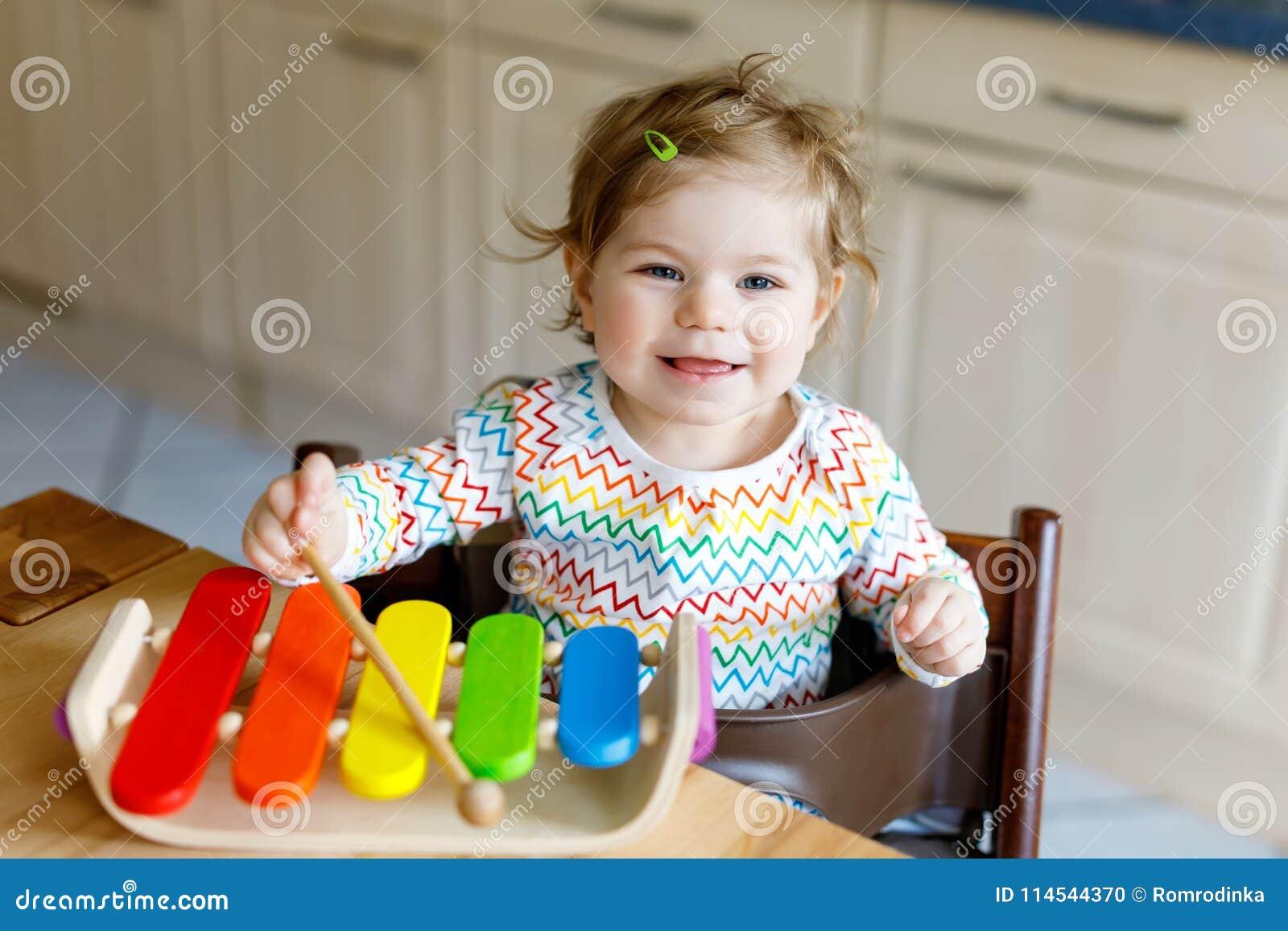 O bebê pequeno bonito bonito adorável que joga com música de madeira educacional brinca em casa ou berçário