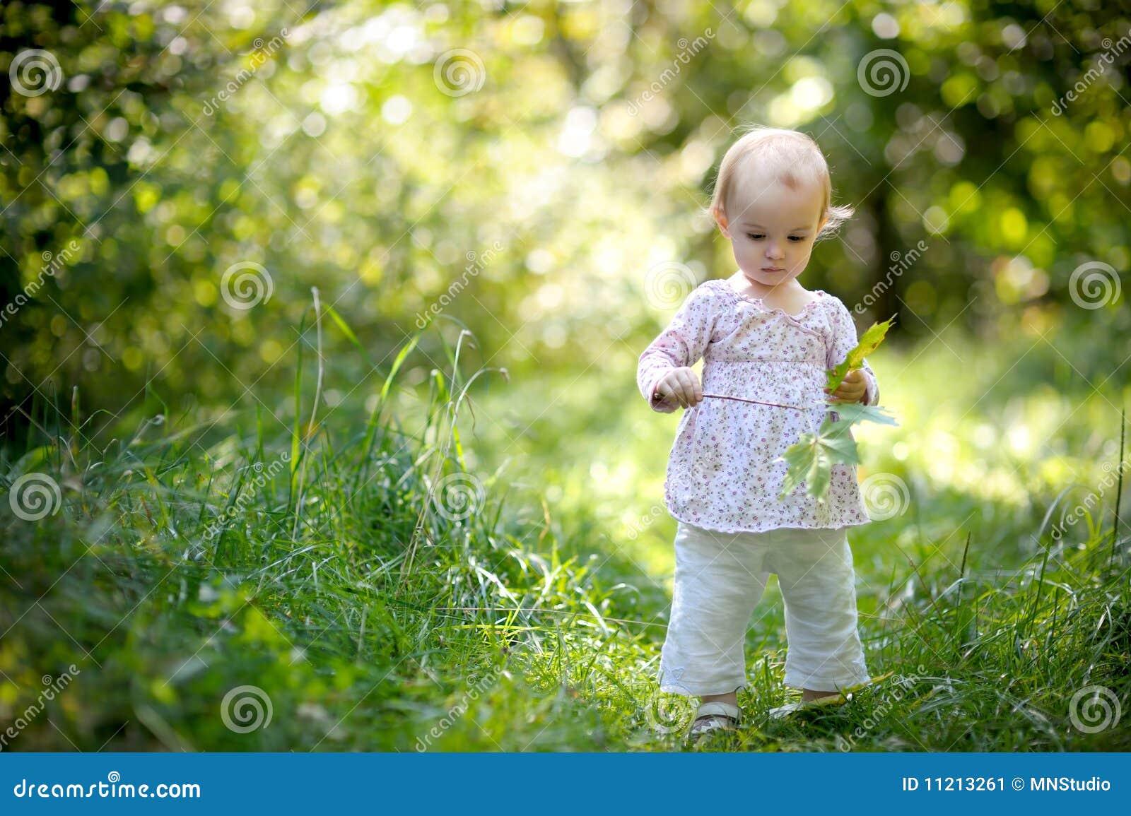 O bebê pequeno em bordos de uma terra arrendada da floresta sae