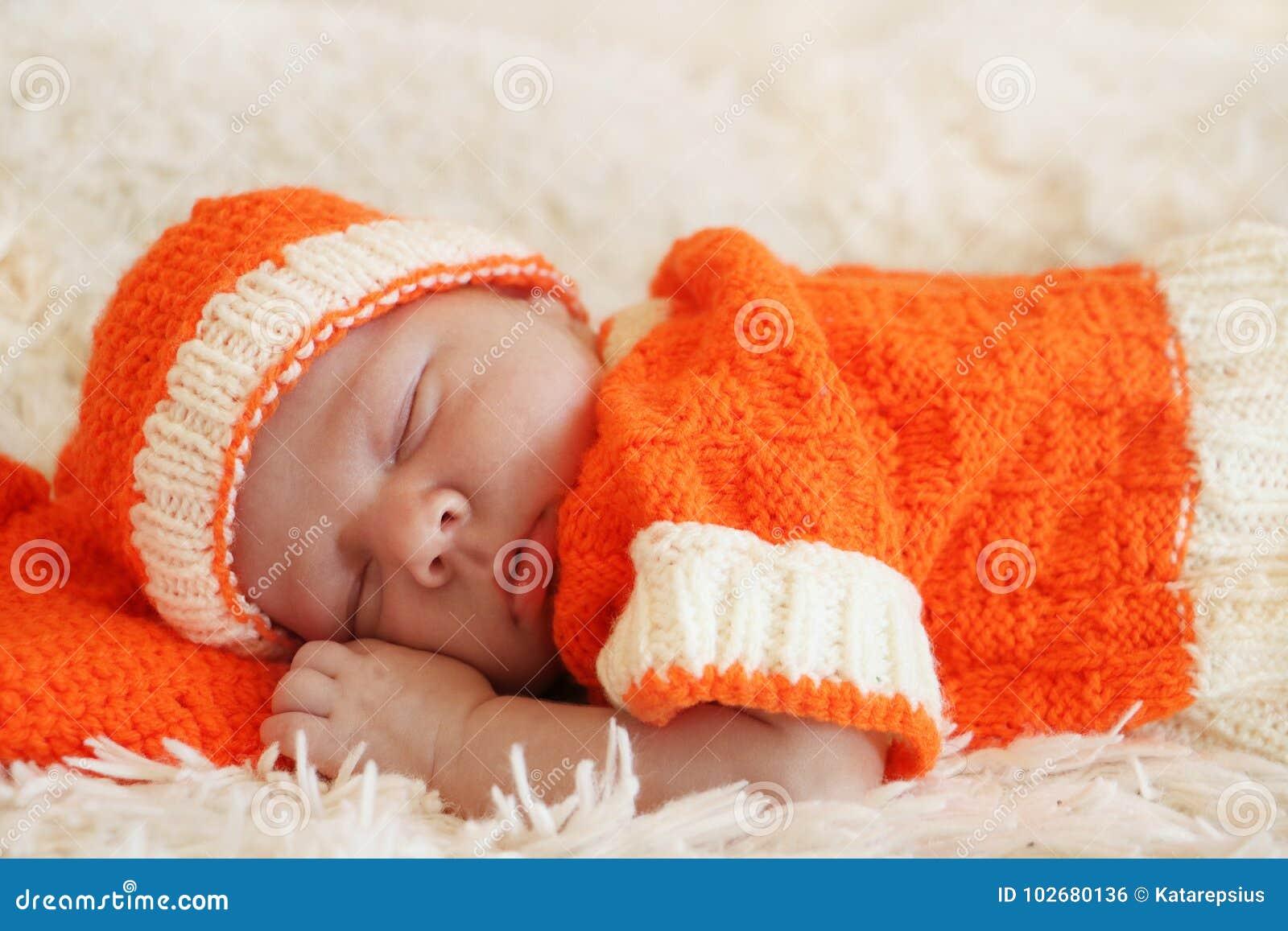 O bebê recém-nascido de sono bonito vestiu-se em um traje alaranjado feito malha o