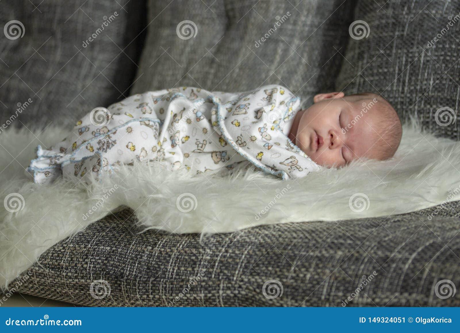 O beb? rec?m-nascido dorme em uma cobertura da pele A crian?a de sono do beb? cresce acima em um sonho Foco macio do retrato
