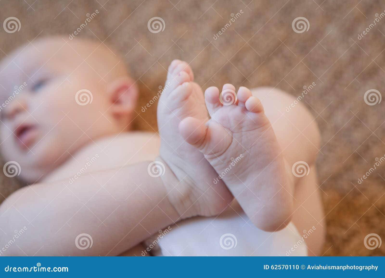 O bebê suporta sobre com pés acima
