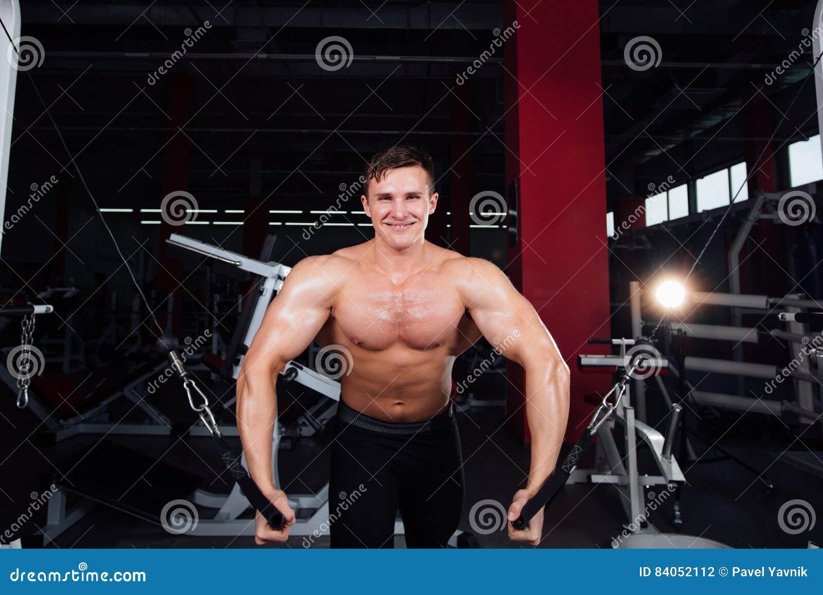 O bodybuider forte grande sem camisas demonstra exercícios do cruzamento Os músculos peitorais e o treinamento duro