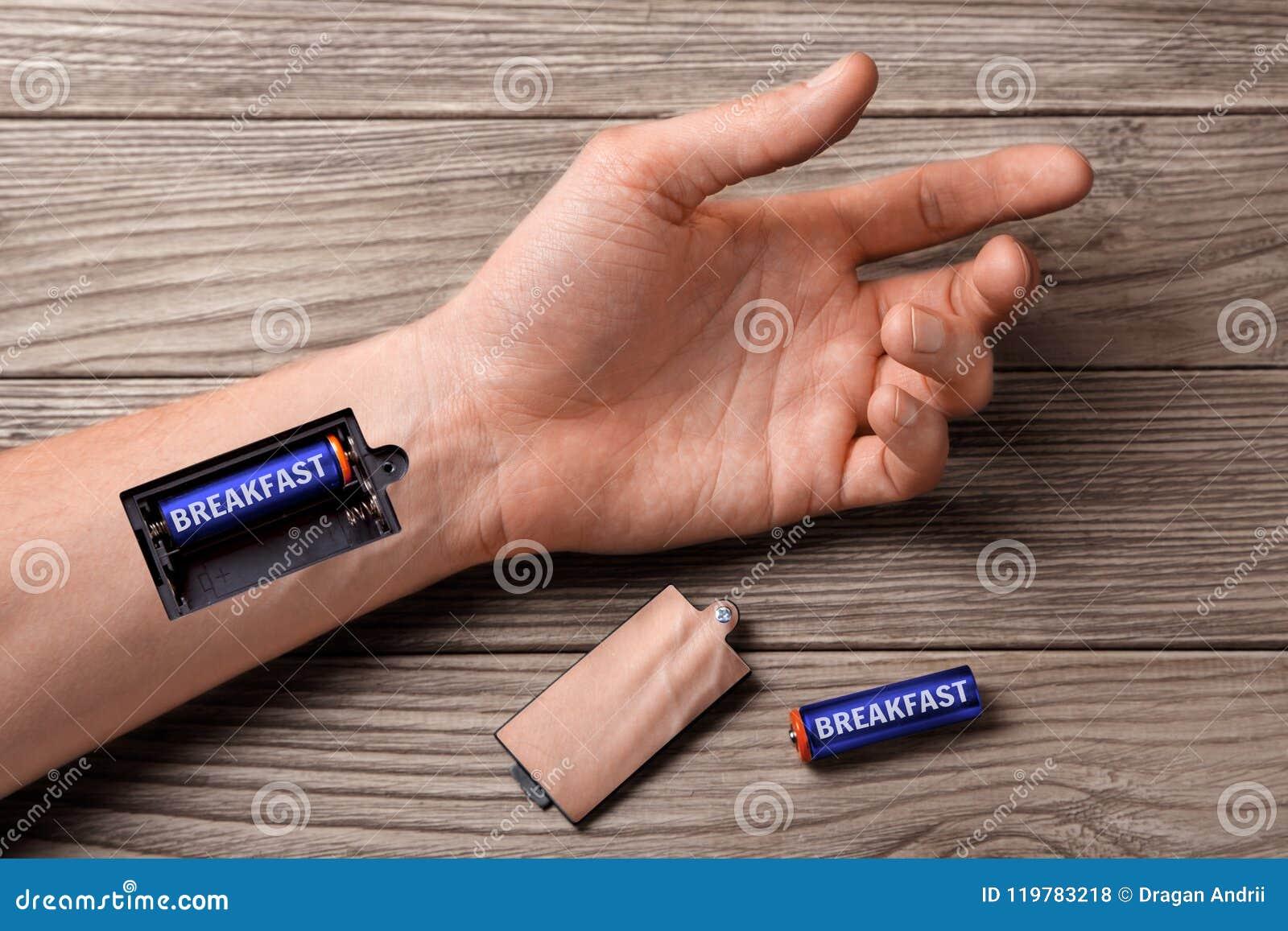 O bom café da manhã energiza o dia inteiro Mão do homem com o entalhe para baterias de carregamento com o café da manhã