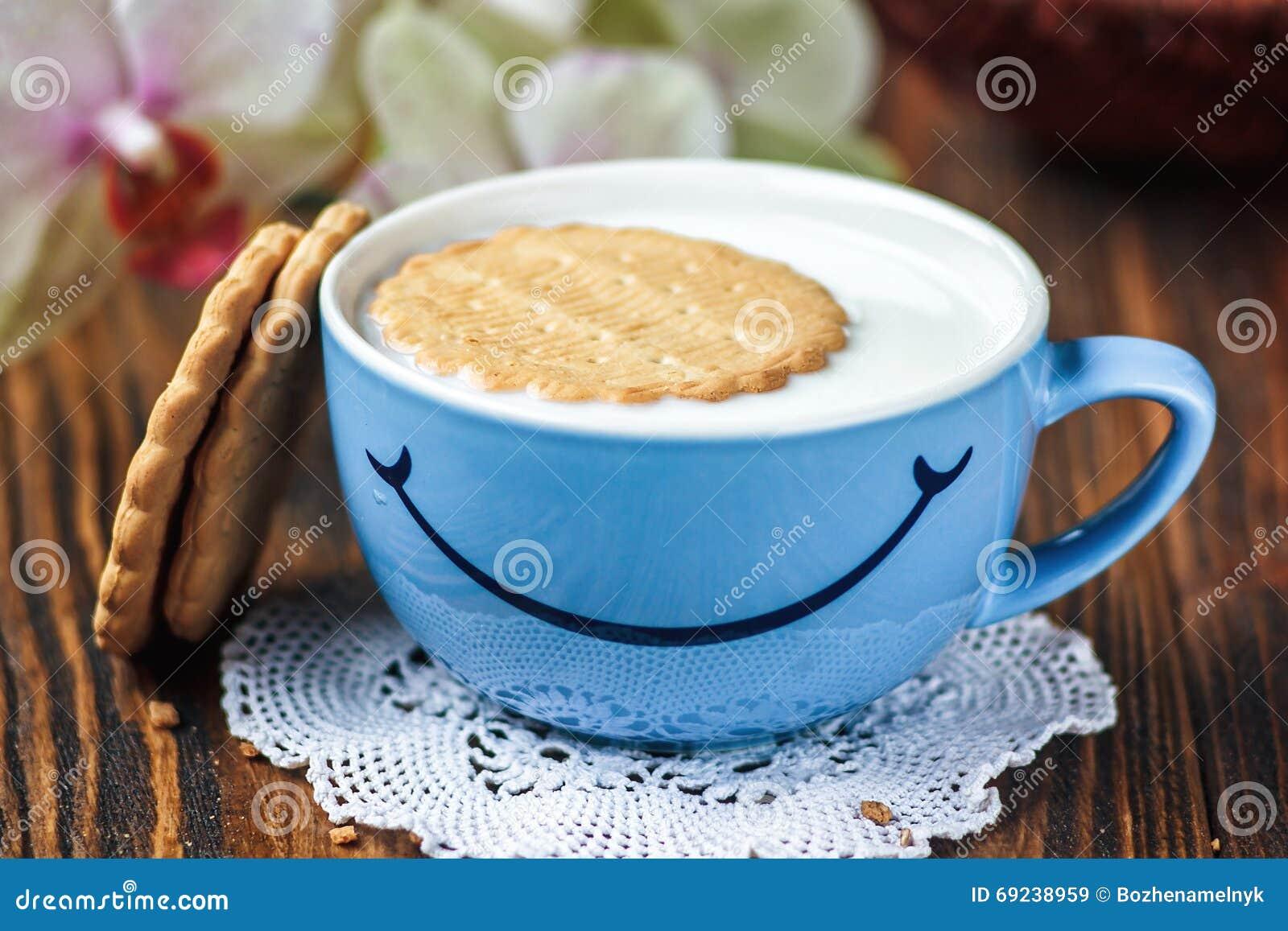 O bom dia ou tem um conceito da mensagem do dia agradável - copo azul brilhante do leite com cookies Copo do leite com sorriso Sa